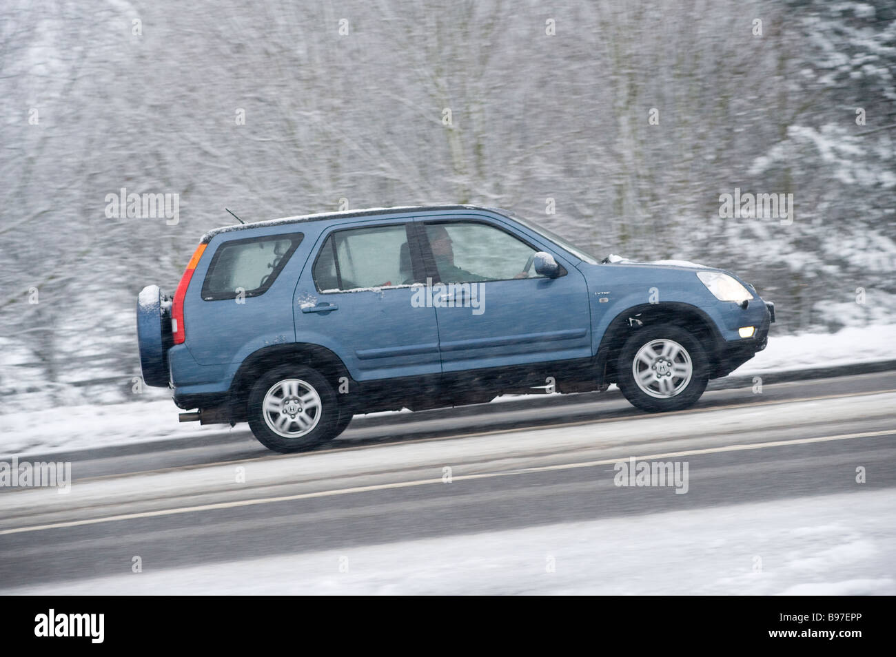 side view of a blue honda hrv 4x4 car driving along a snow. Black Bedroom Furniture Sets. Home Design Ideas