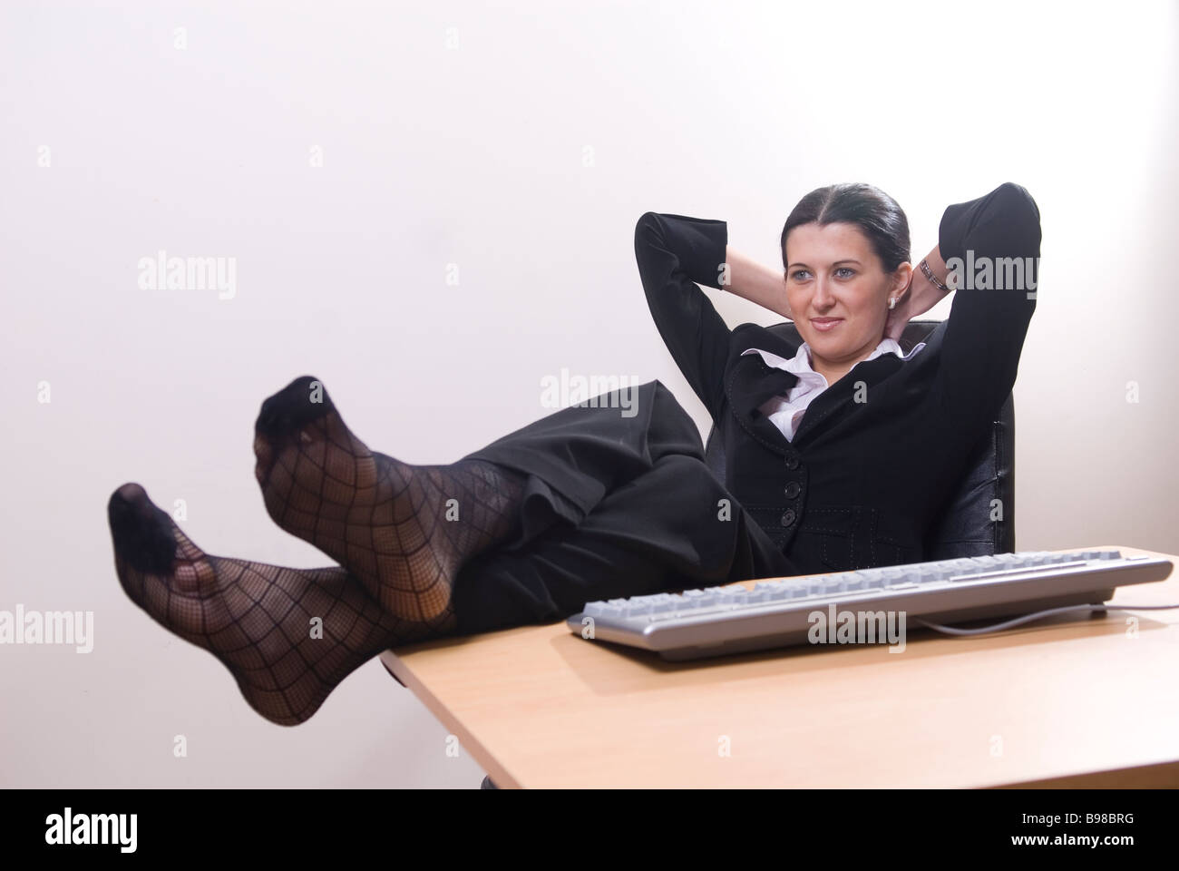Business Woman Sitting In Office Feet On Desk And Hands