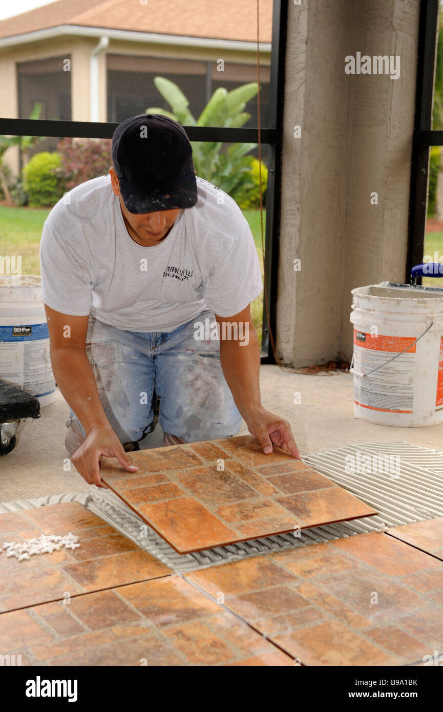 Male hispanic lays ceramic tile on cement floor in patio lanai male hispanic lays ceramic tile on cement floor in patio lanai dailygadgetfo Gallery