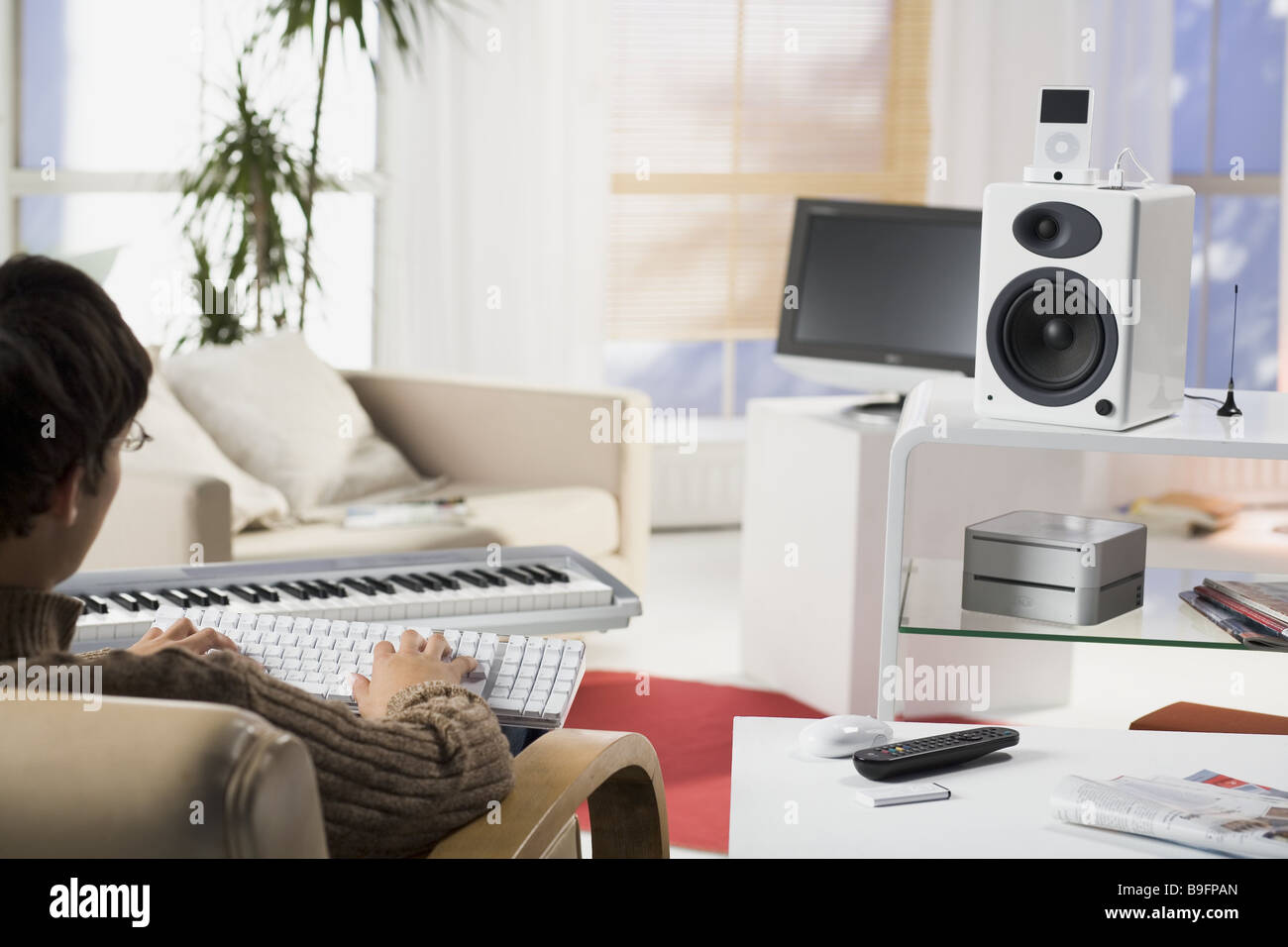 Living Room With Tv And People living room man young sitting keyboard data input back view detail
