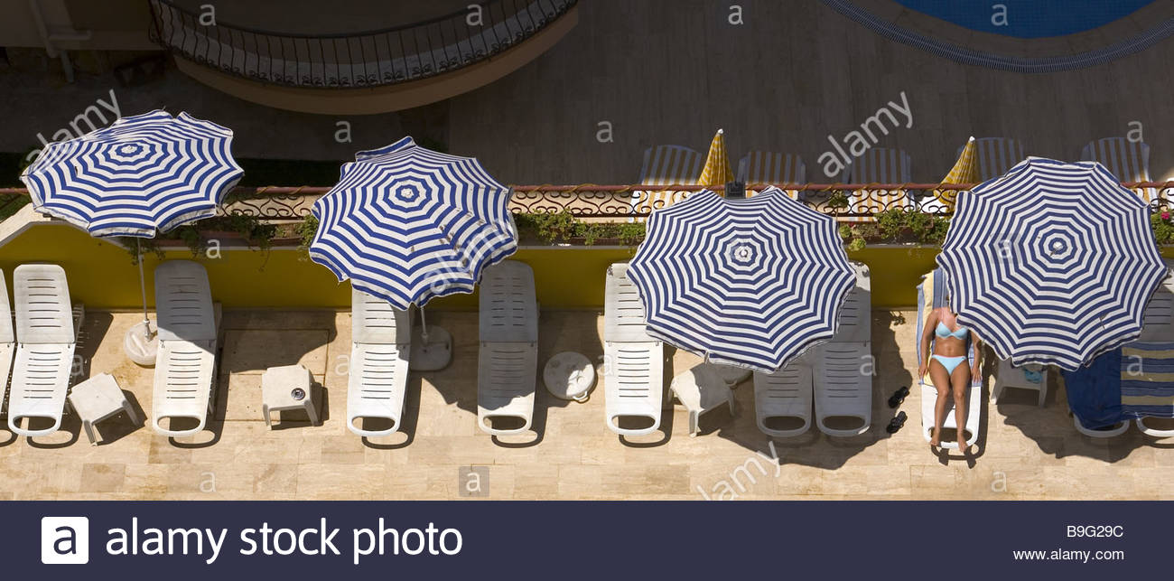 Pool chair top view - Stock Photo Turkey Alanya Hotel Terrace Woman Deck Chair Sunbath Top View Hotel Installation Hotel Pool Installation Sun Loungers Parasols