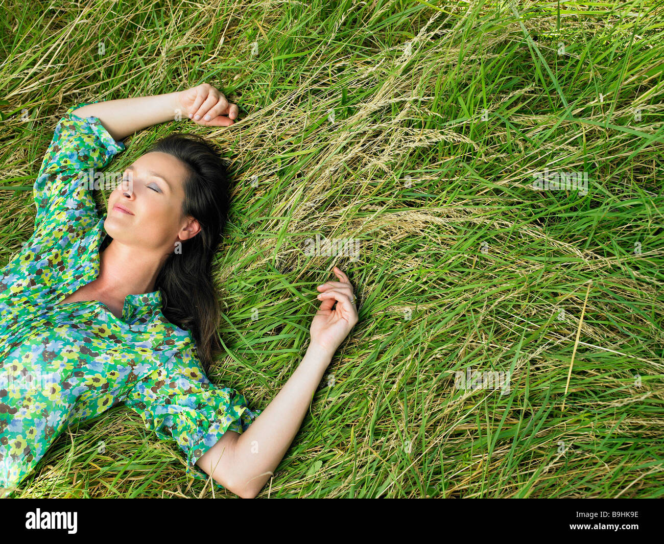 Woman laying down in a field Stock Photo, Royalty Free ...