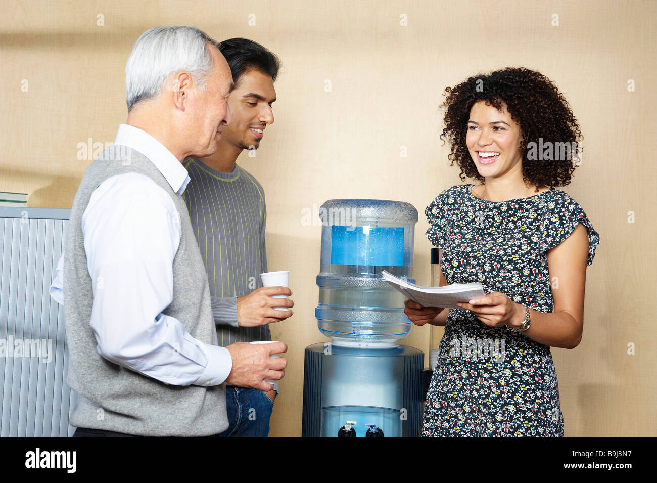 Casual meeting by office water cooler Stock Photo, Royalty Free ...