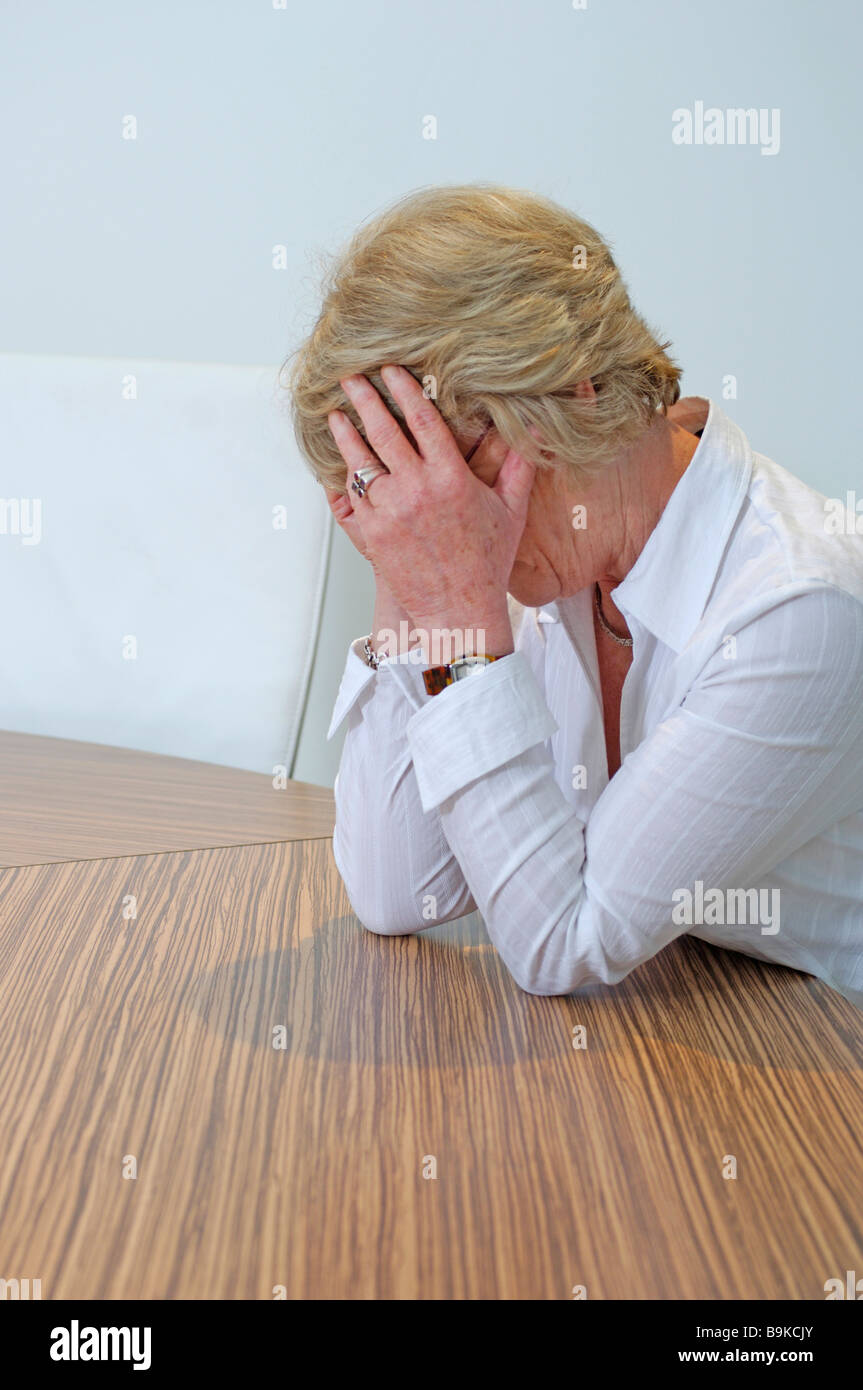 Stock Photo   Mature Businesswoman Sitting At Table Covering Her Face In  Despair