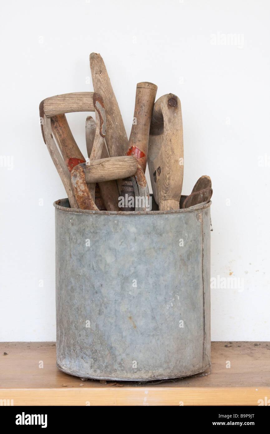 A Tin Of Garden Tool Handles On A Wooden Bench