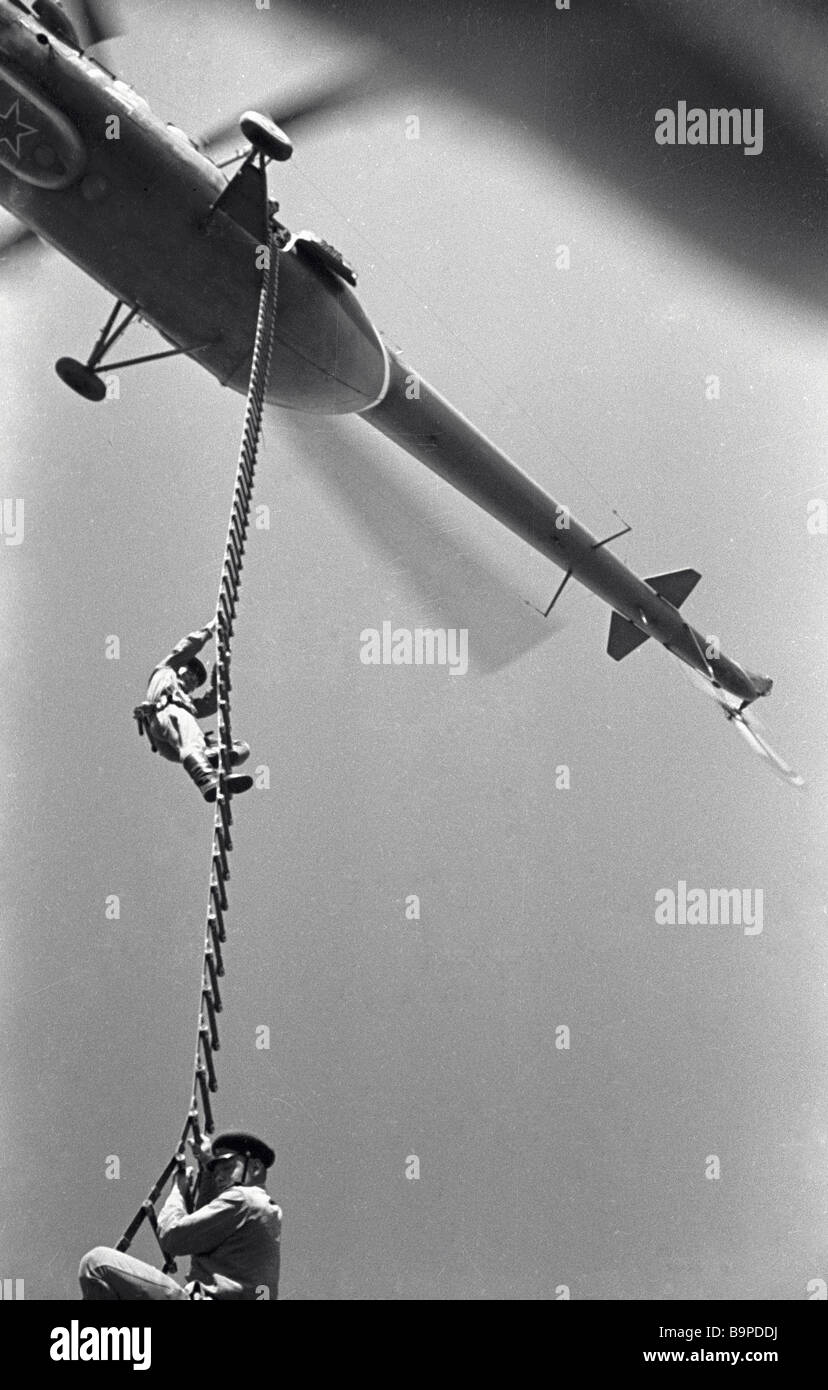 frontier guards climbing up the rope ladder of a helicopter stock frontier guards climbing up the rope ladder of a helicopter