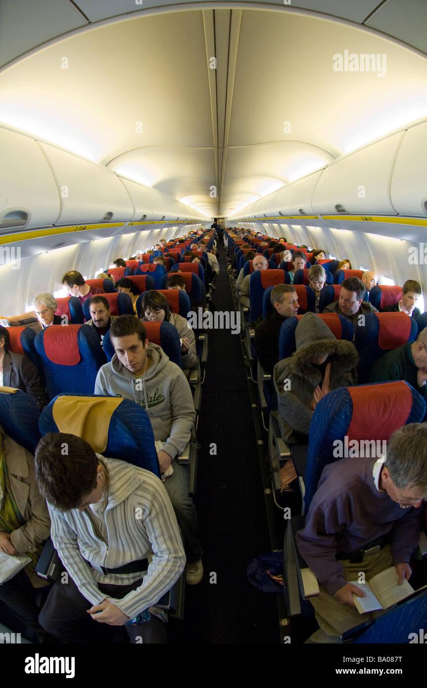 Boeing 737 800 aircraft inside image - Passengers In Cabin Ryanair Boeing 737 800 Airplane Luton Airport England Uk Europe
