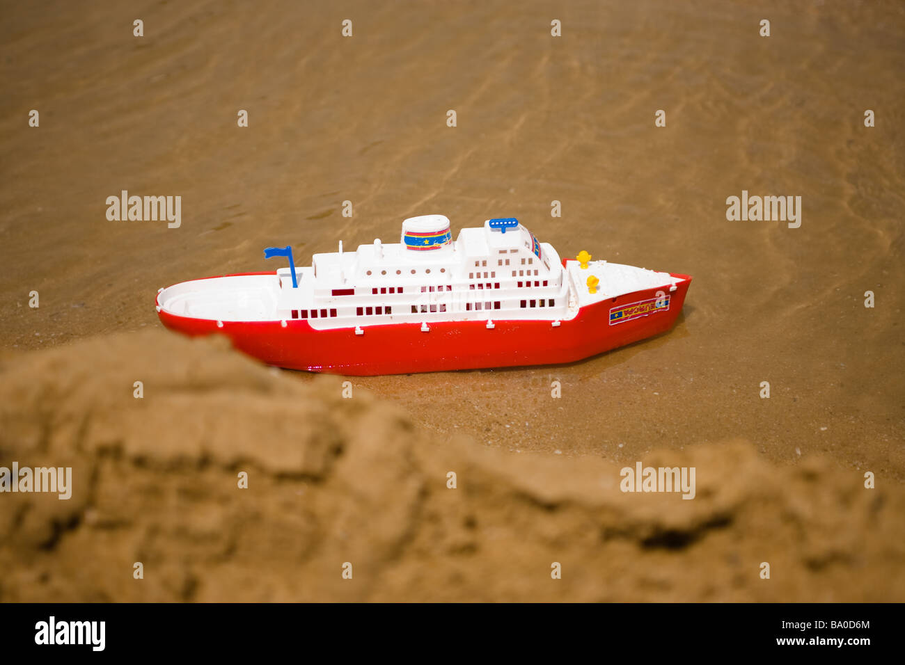 A Toy Cruise Ship Floats In A Sea Water Pond Behind The Sand Ridge - Toy cruise ship