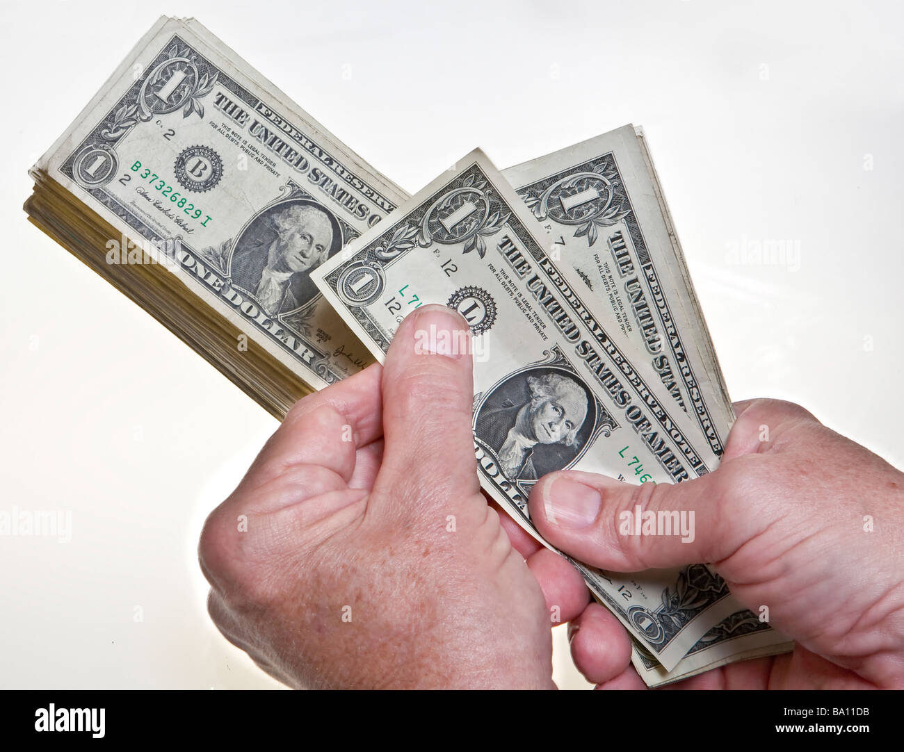 worksheet Counting Dollar Bills older mans hands counting one dollar bills onto a stack on white background