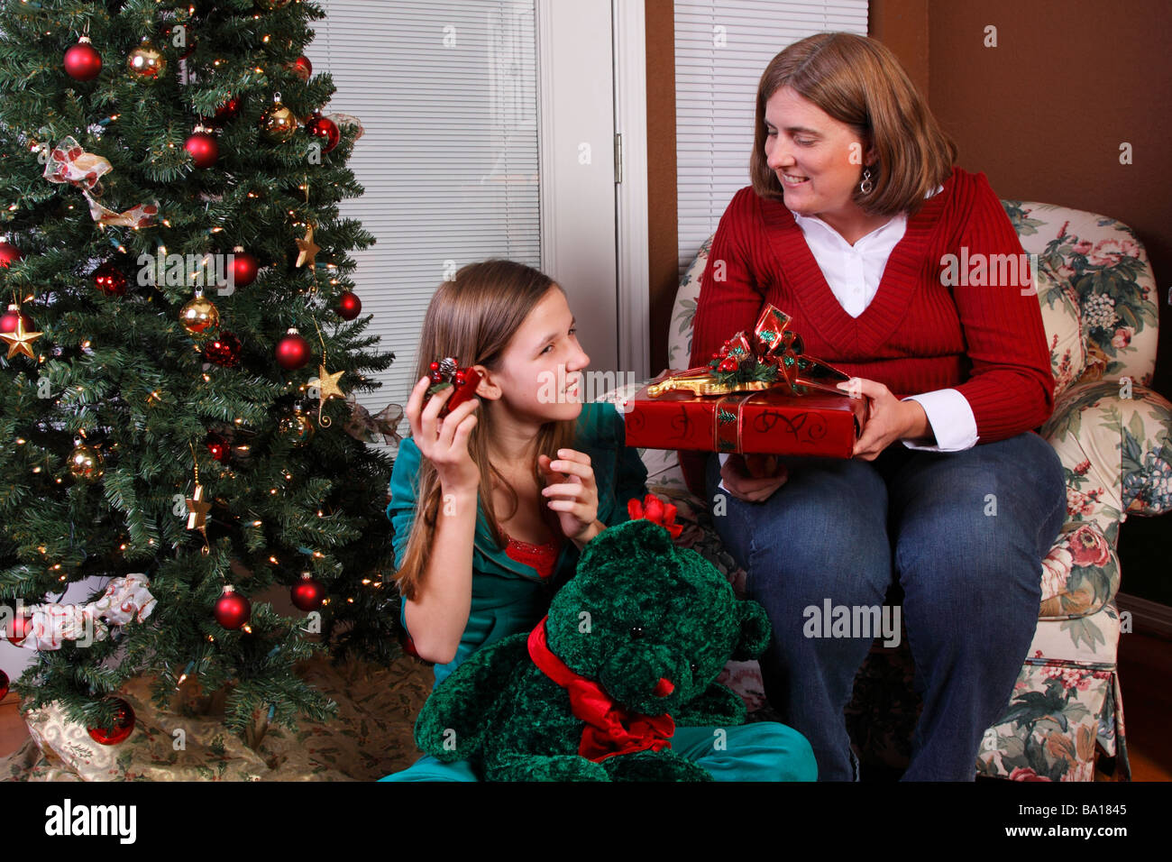 Mom And Daughter Exchanging Christmas Gifts Stock Photo