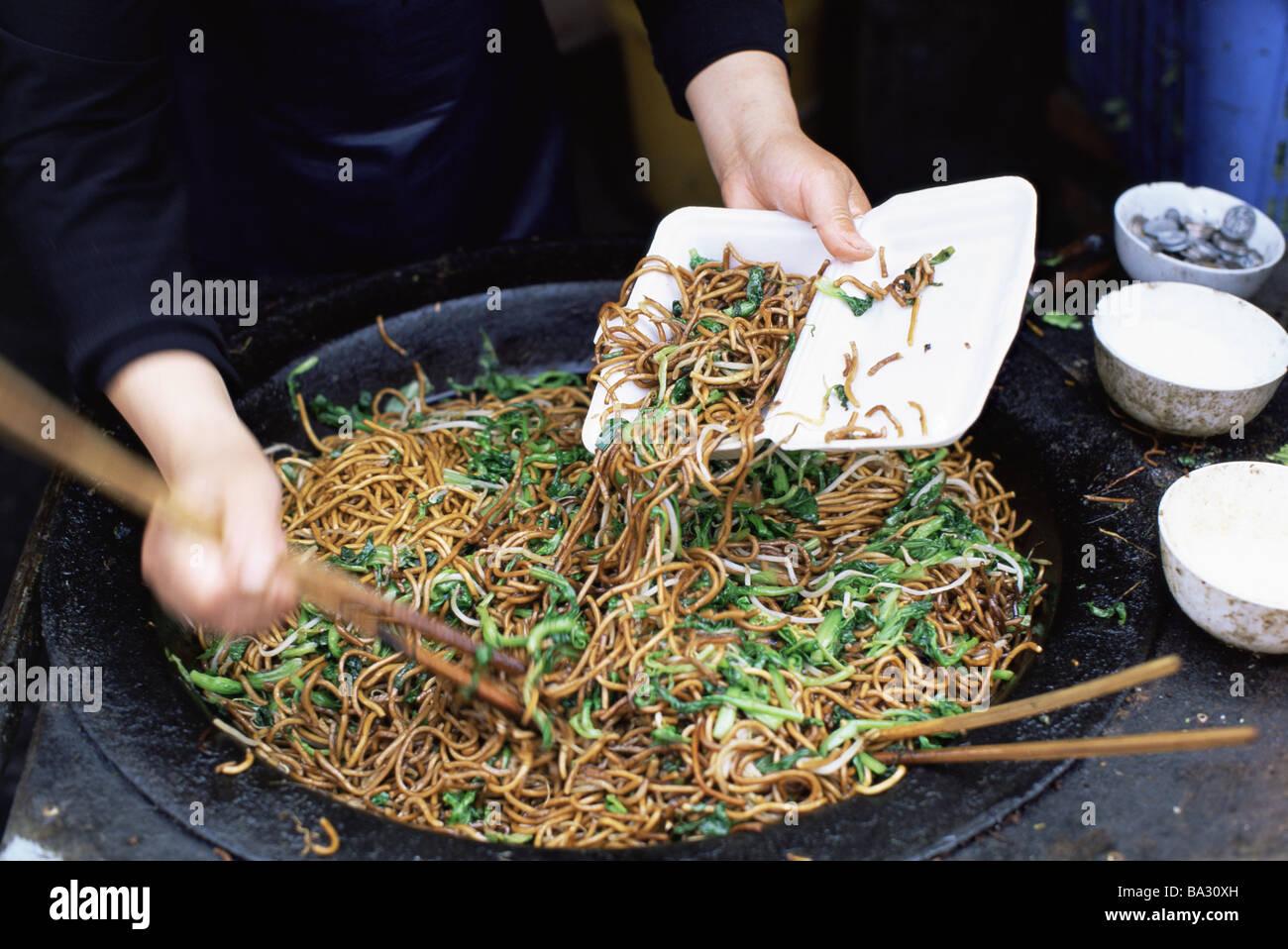 china shanghai garküche detail wok noodle-court person hands peel