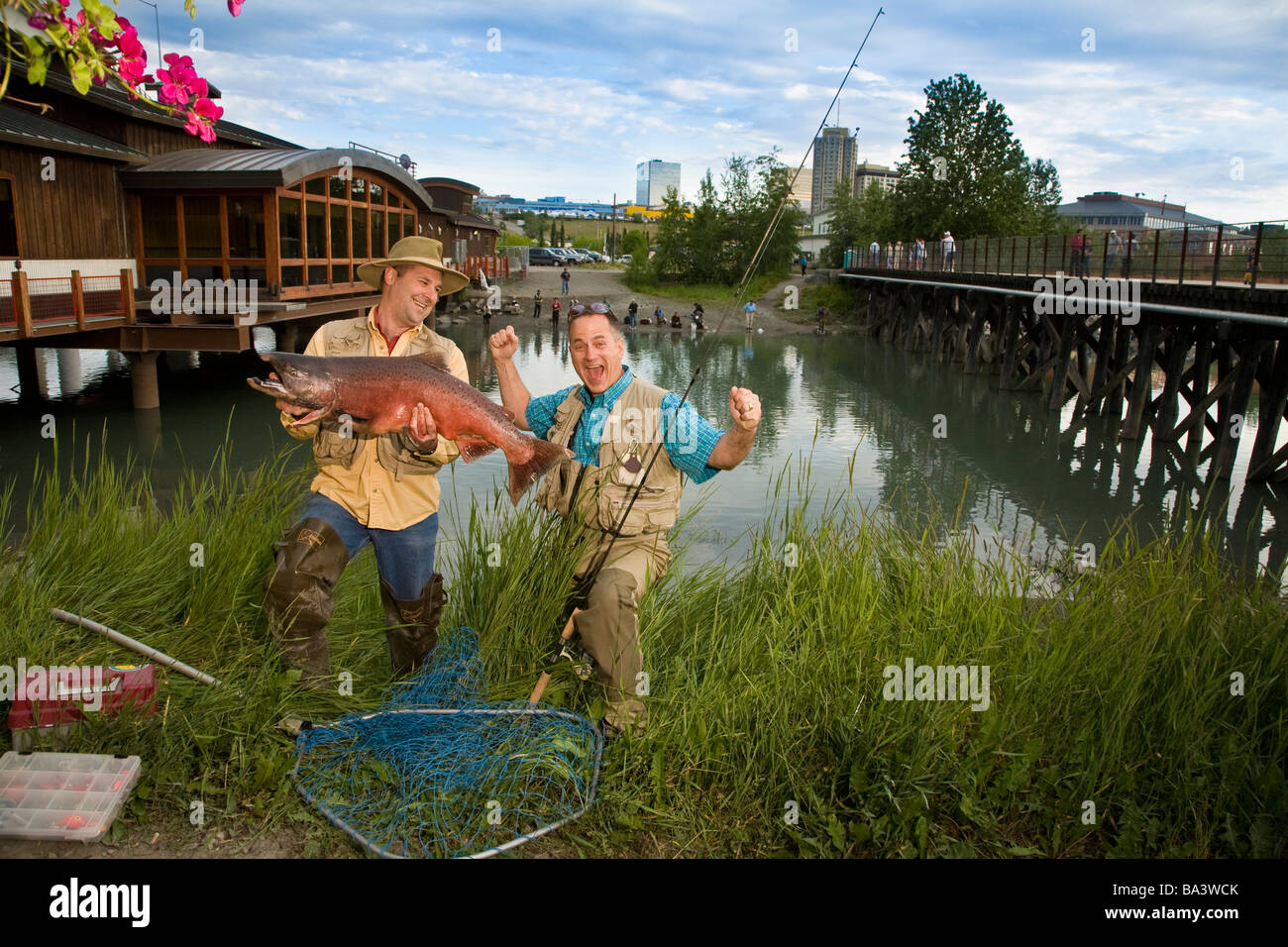 Fishermen poses with king salmon at ship creek in downtown for Salmon fishing anchorage