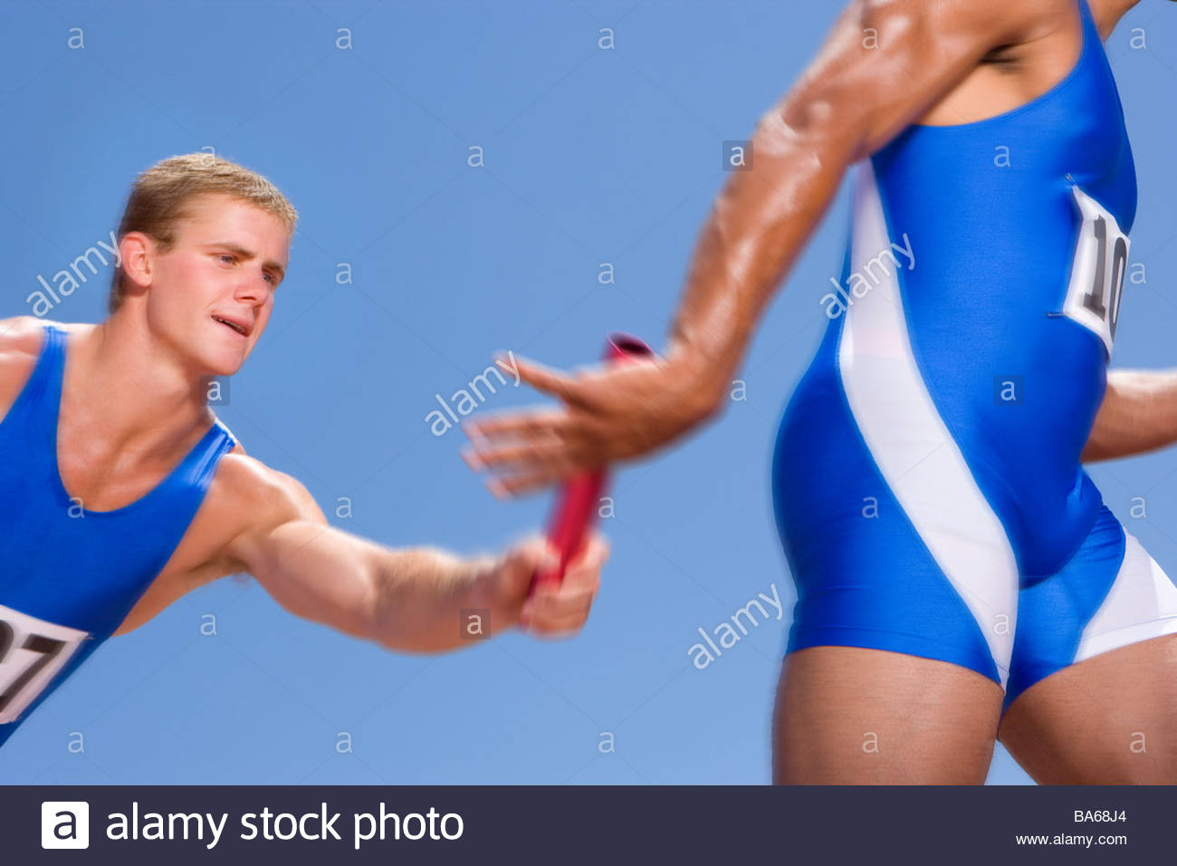 Young male athletes passing relay race baton Stock Photo, Royalty ...
