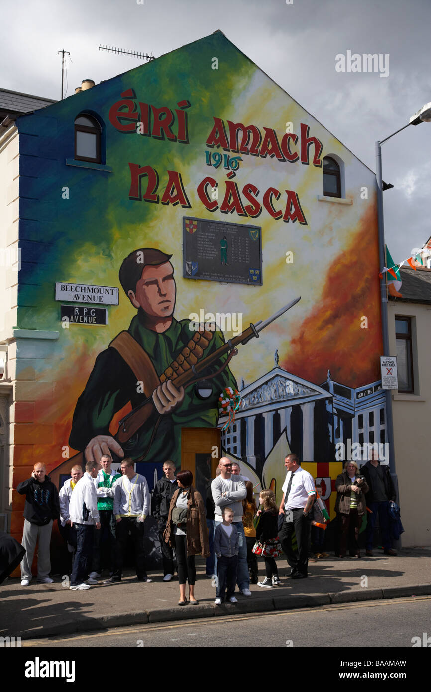 People gather on beechmount avenue beneath the easter for Easter rising mural
