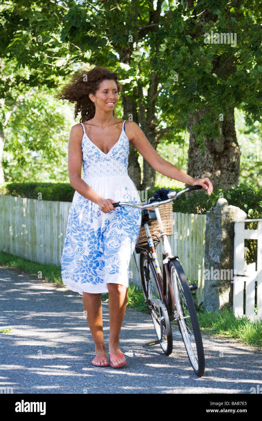 A Woman Walking With A Bike In The Swedish Countryside Stock Photo