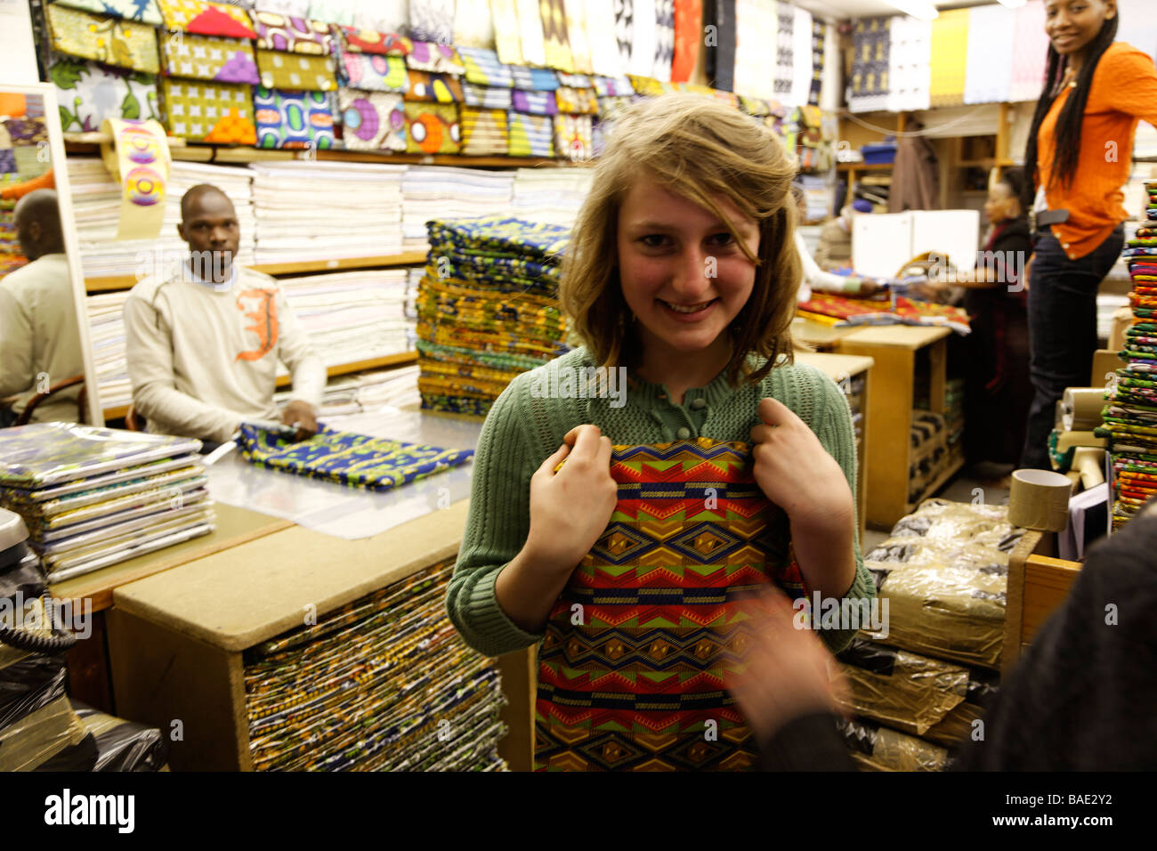 Stock Photo   White teenage girl shopping for material to make clothes in  African shop Petticoat Lane London. White teenage girl shopping for material to make clothes in