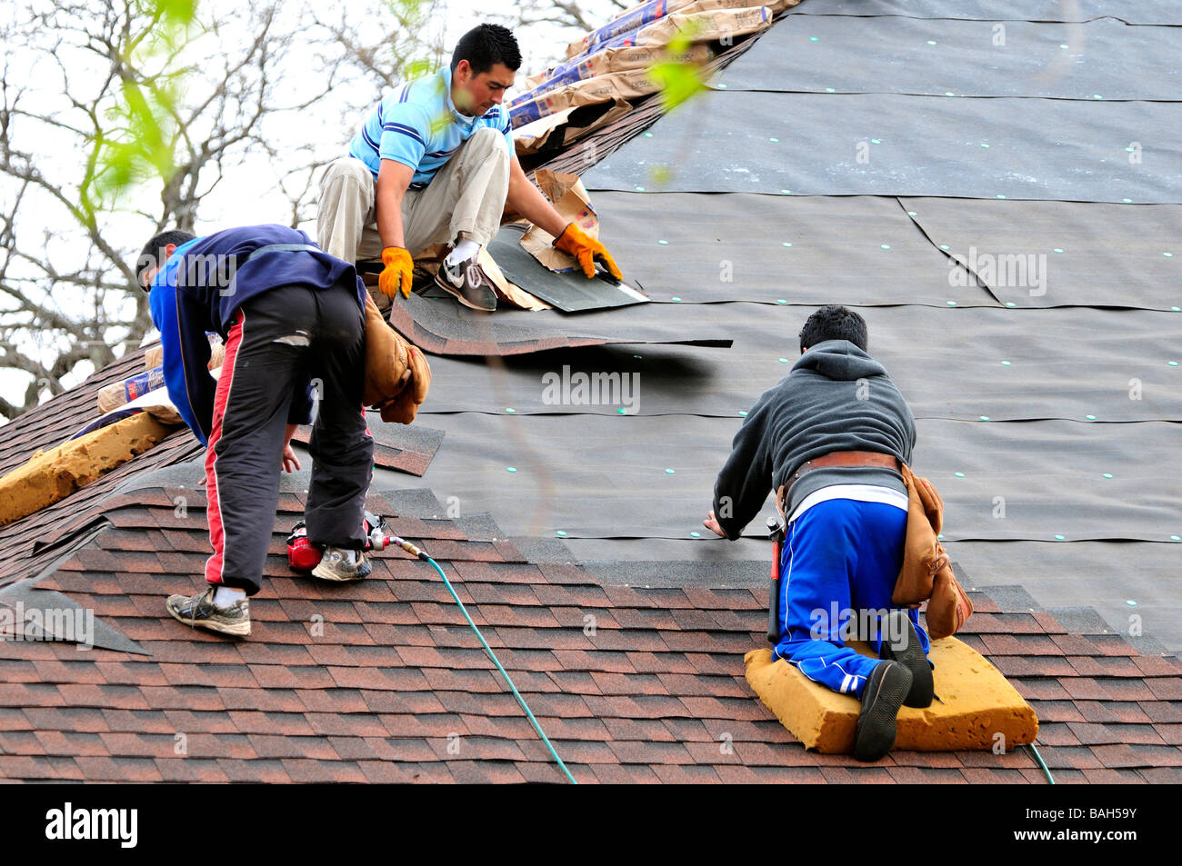 Hispanic Men Put Shingles On The Roof Of A New House In Oklahoma City,  Oklahoma, USA.