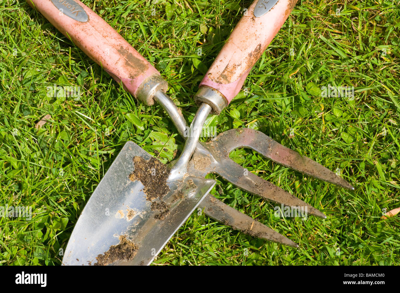 Gardening garden tools hand trowel and fork laying on the for Hand tools for planting