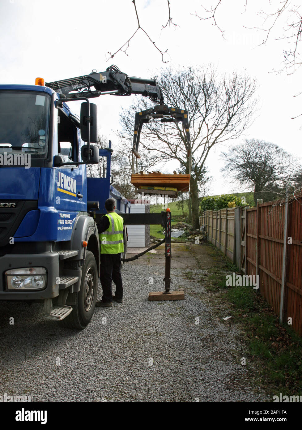 Builders merchant stock photos builders merchant stock images a builders merchant delivering wooden fence panels with a lorry with a hydraulic lifting arm baanklon Choice Image