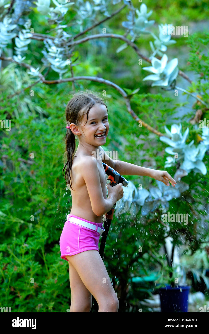 Seven Year Old Girl Playing With Hose In Backyard Garden