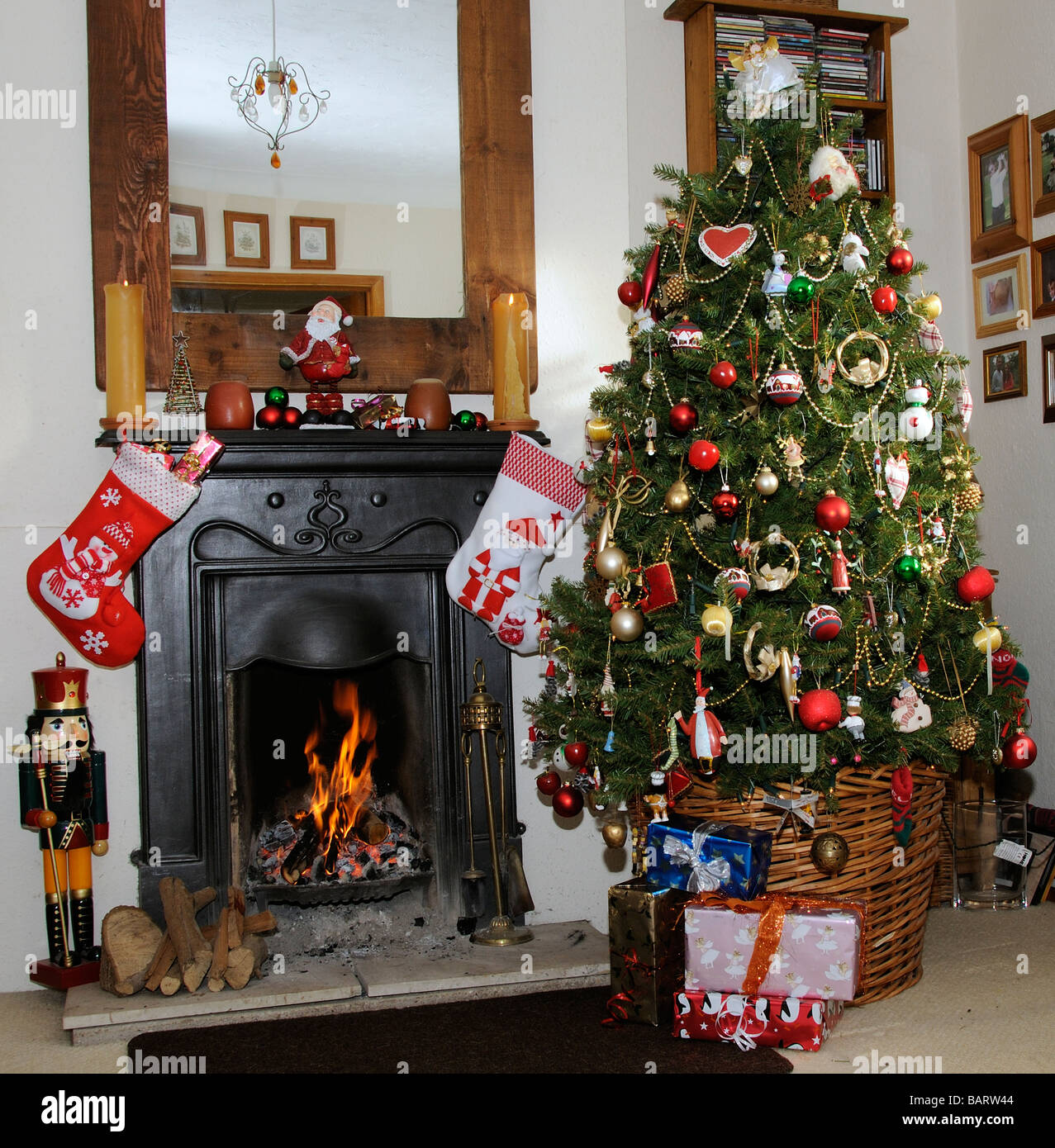 Real christmas trees with presents - Christmas Tree With Presents And Colourful Xmas Decorations Standing By An Open Fire