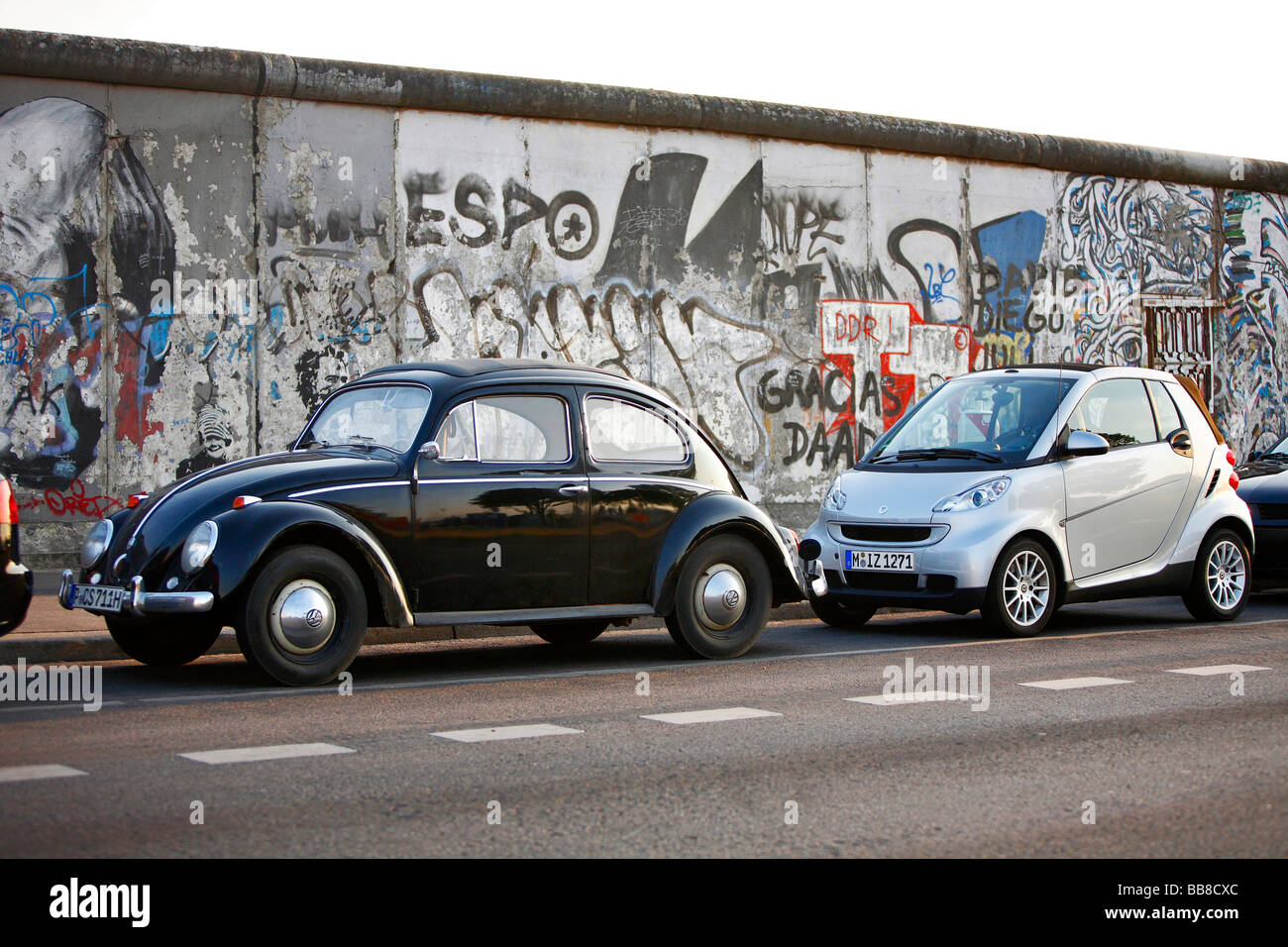 generations of small cars volkswagen beetle and smart fortwo at the east side gallery in