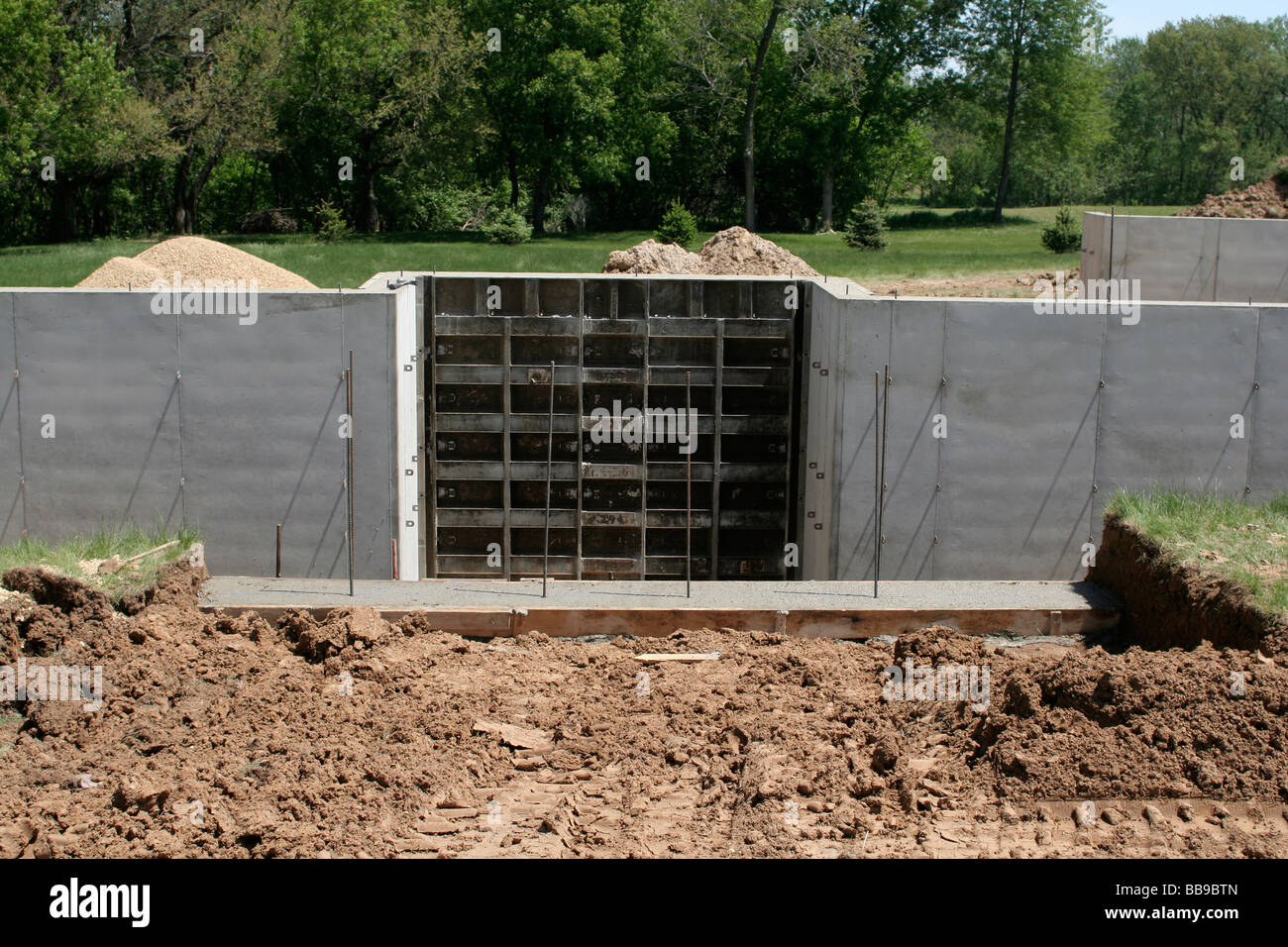 Poured concrete basement wall with section of forms for Basement wall forms