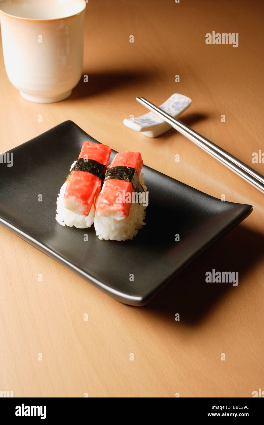 2 pieces of sushi, kanikama nigiri, crabstick on tray with