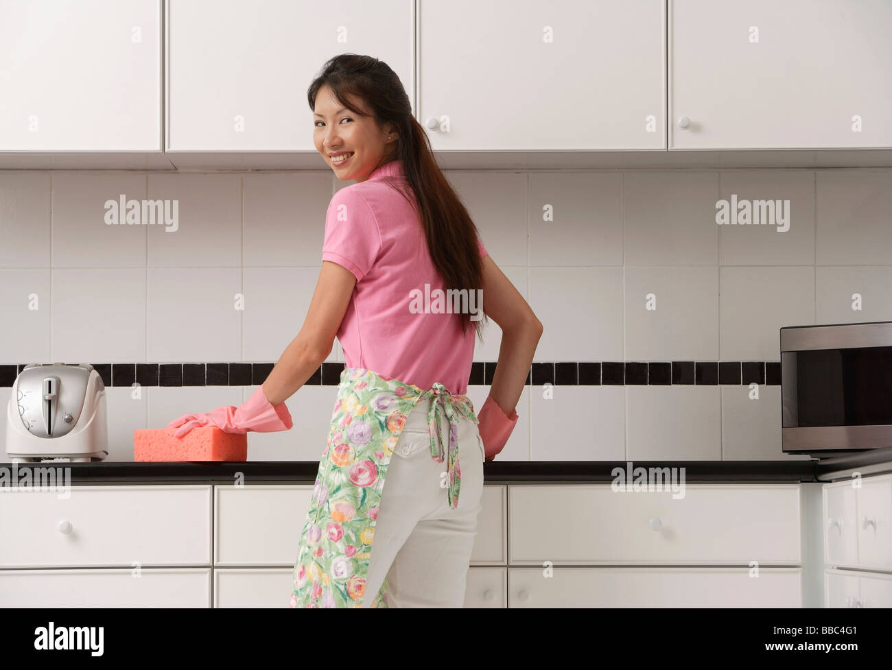 White gloves apron cleaning services - Woman Standing In Kitchen Wearing Gloves And Apron Cleaning Counter With Pink Sponge Looking Over Shoulder