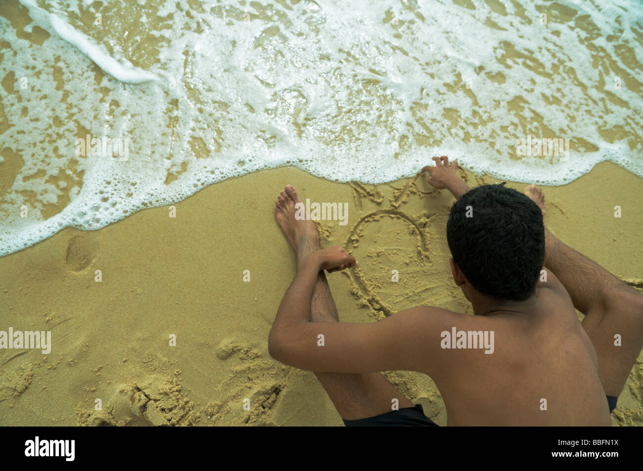 The Boy Drawing A Heart On Send At Water Edge Beach