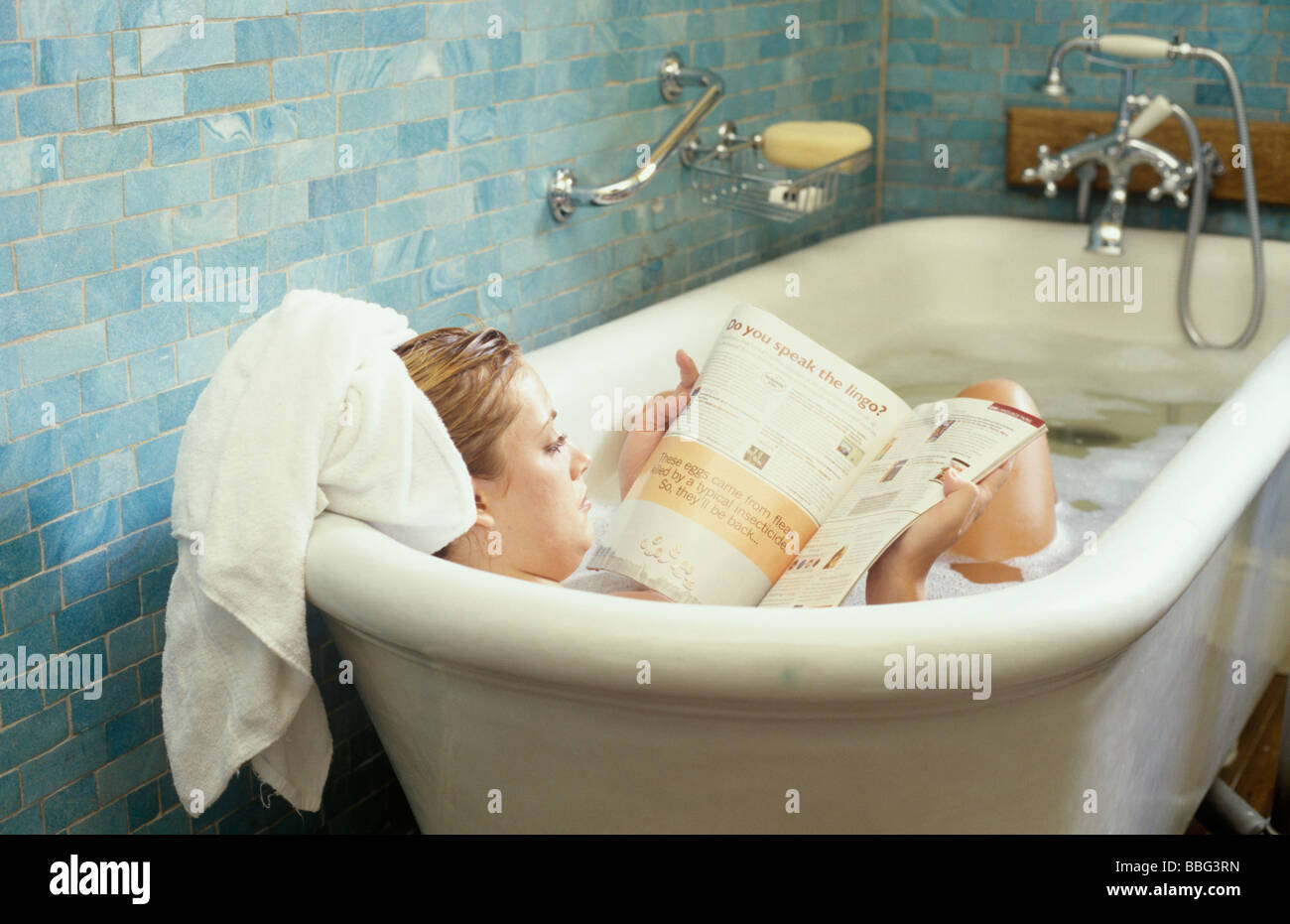 woman reading a magazine in the bath