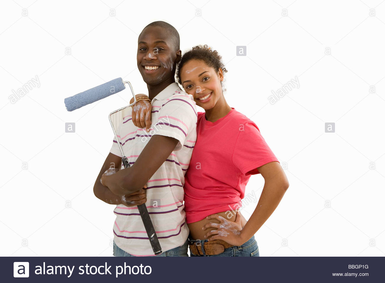 young couple home decorating man with paint roller woman embracing man smiling portrait cut out