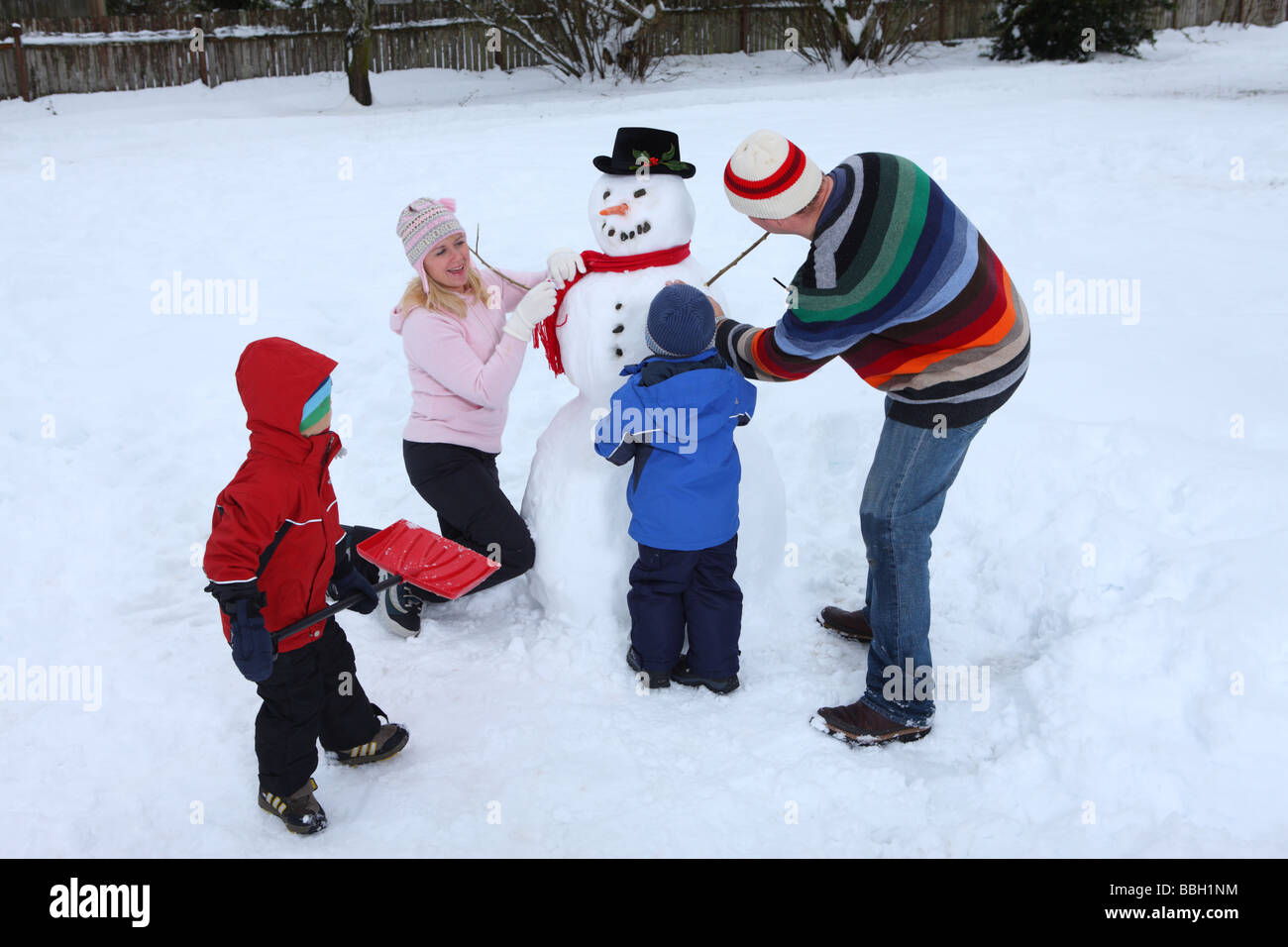 Family making a snowman stock photo royalty free image for How to make a snowman