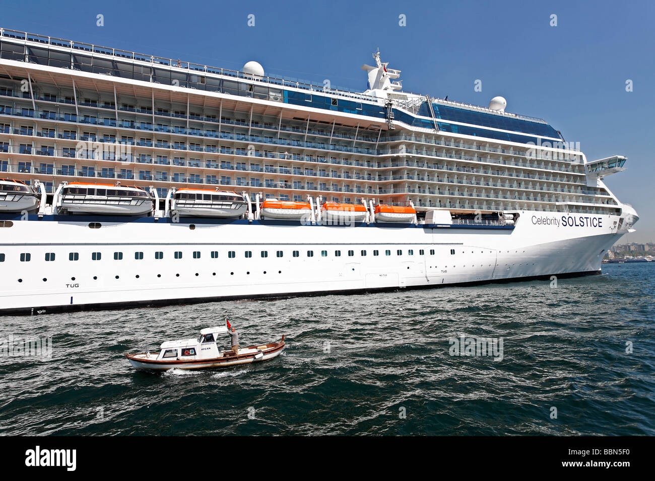 Tiny Boat Goes Past The Huge Cruise Ship Celebrity Solistice Stock - Huge cruise ship