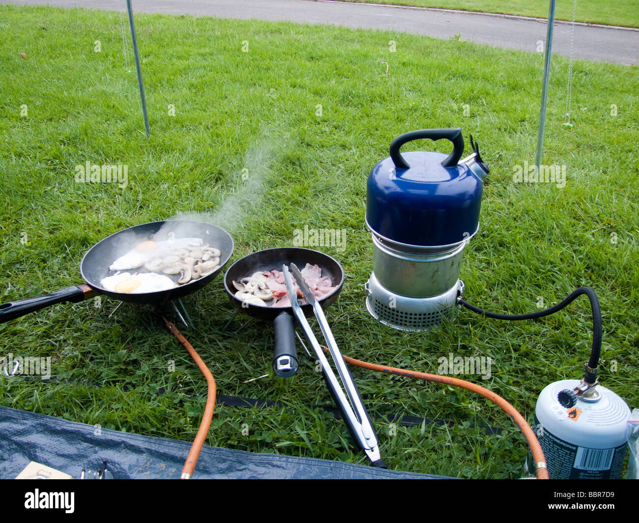 Open air cooking making breakfast while c&ing in a tent & Open air cooking making breakfast while camping in a tent Stock ...