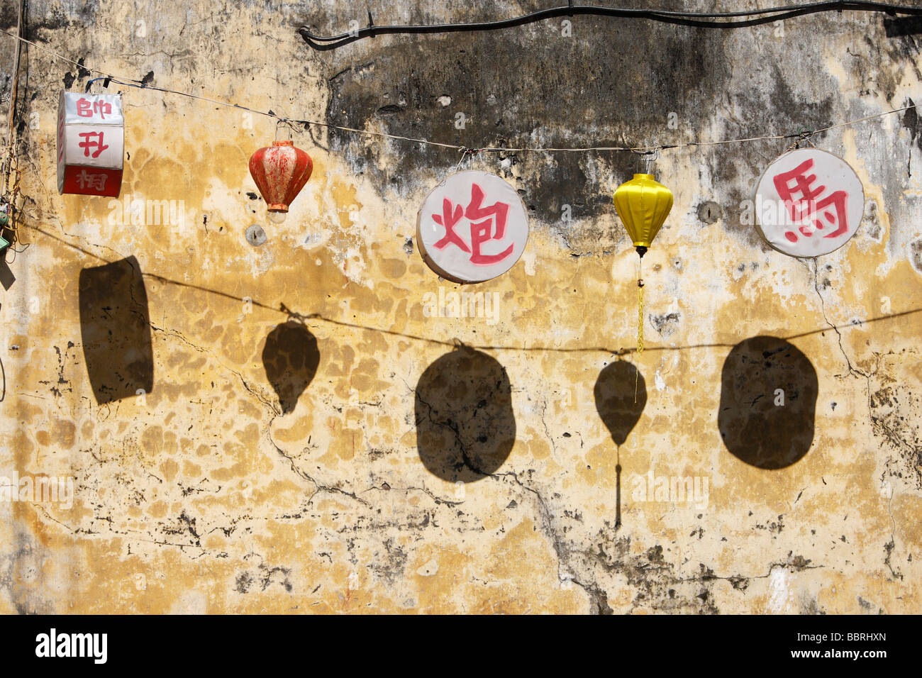 Oriental lanterns hanging against old wall, \