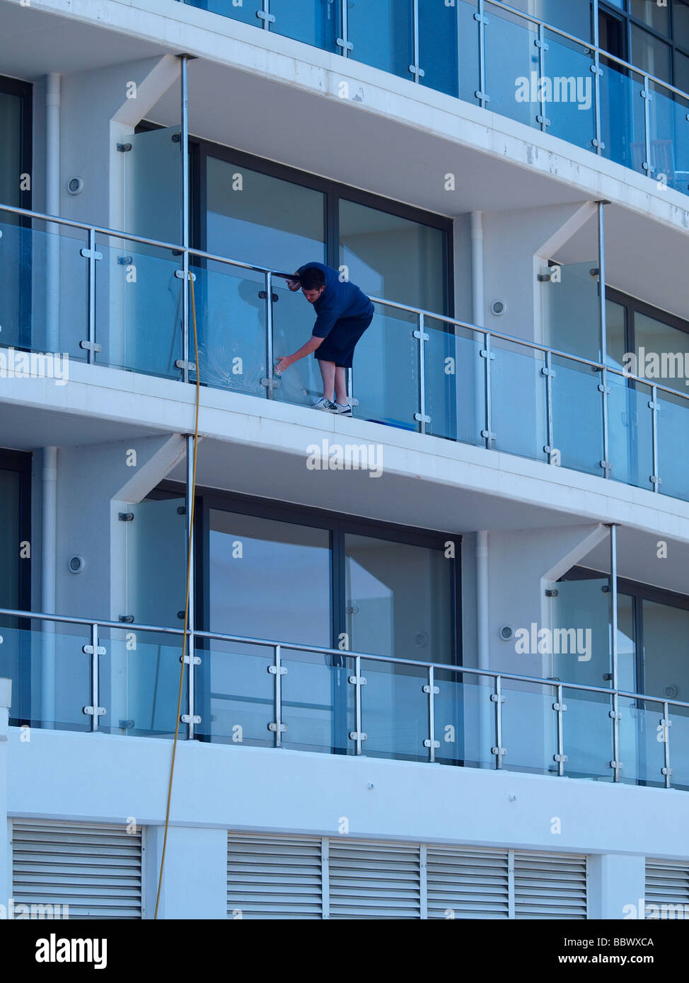 Man Cleaning Glass Panels Of Balcony On A Block Of Flats