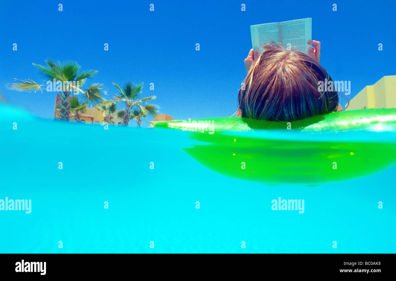 Inflatable bed clear - Stock Photo Woman 40 Floating On Inflatable Airbed On Clear Blue Water Swimming Pool Reading A Book Palm Trees Background
