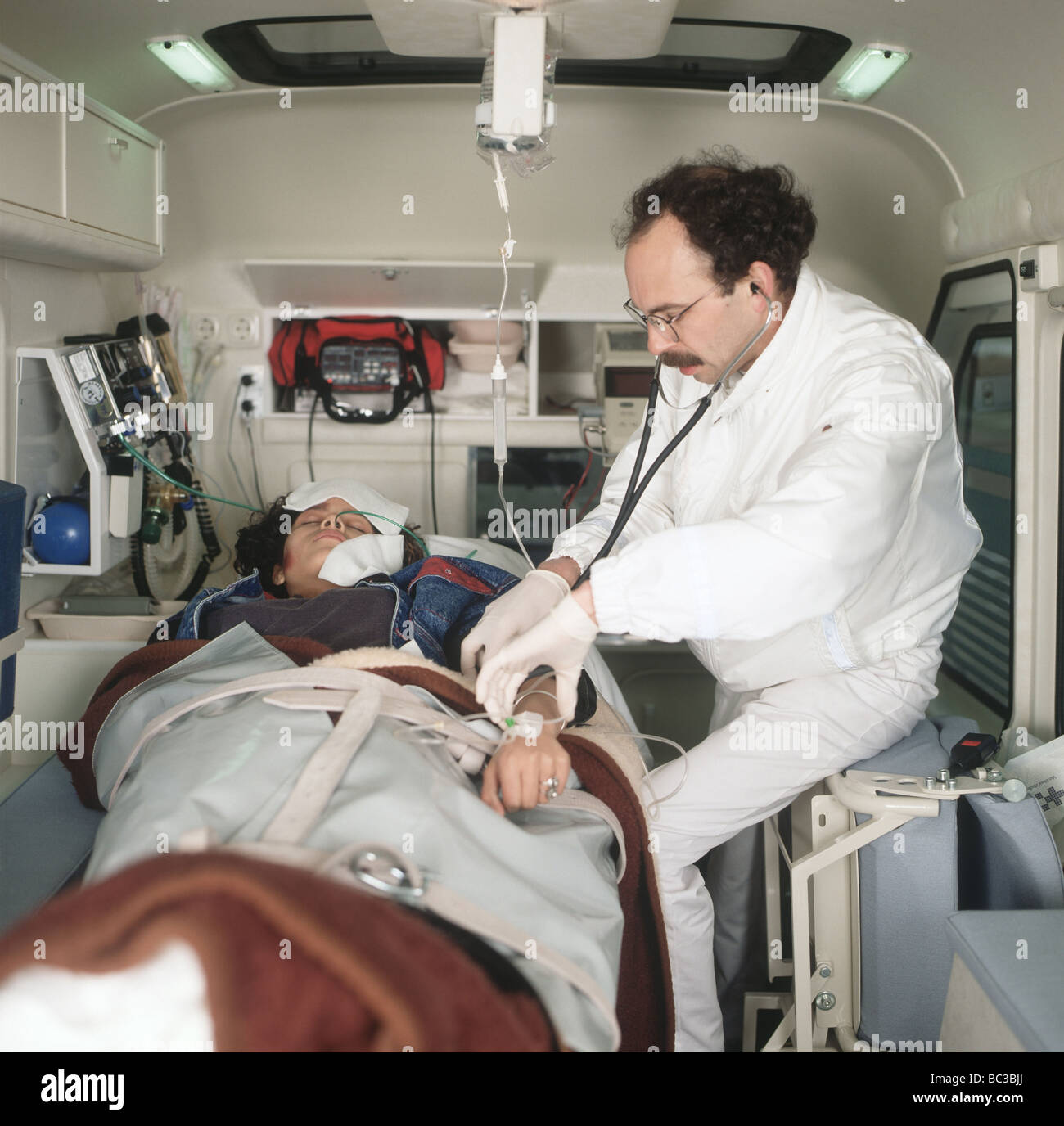 Paramedic examines a patient inside an ambulance,, IV bag ...