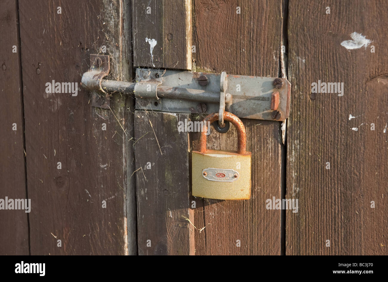Sliding door bolt stock photos sliding door bolt stock images close up of locked rusty padlock securing sliding door bolt on wood clad garageshed vtopaller Image collections