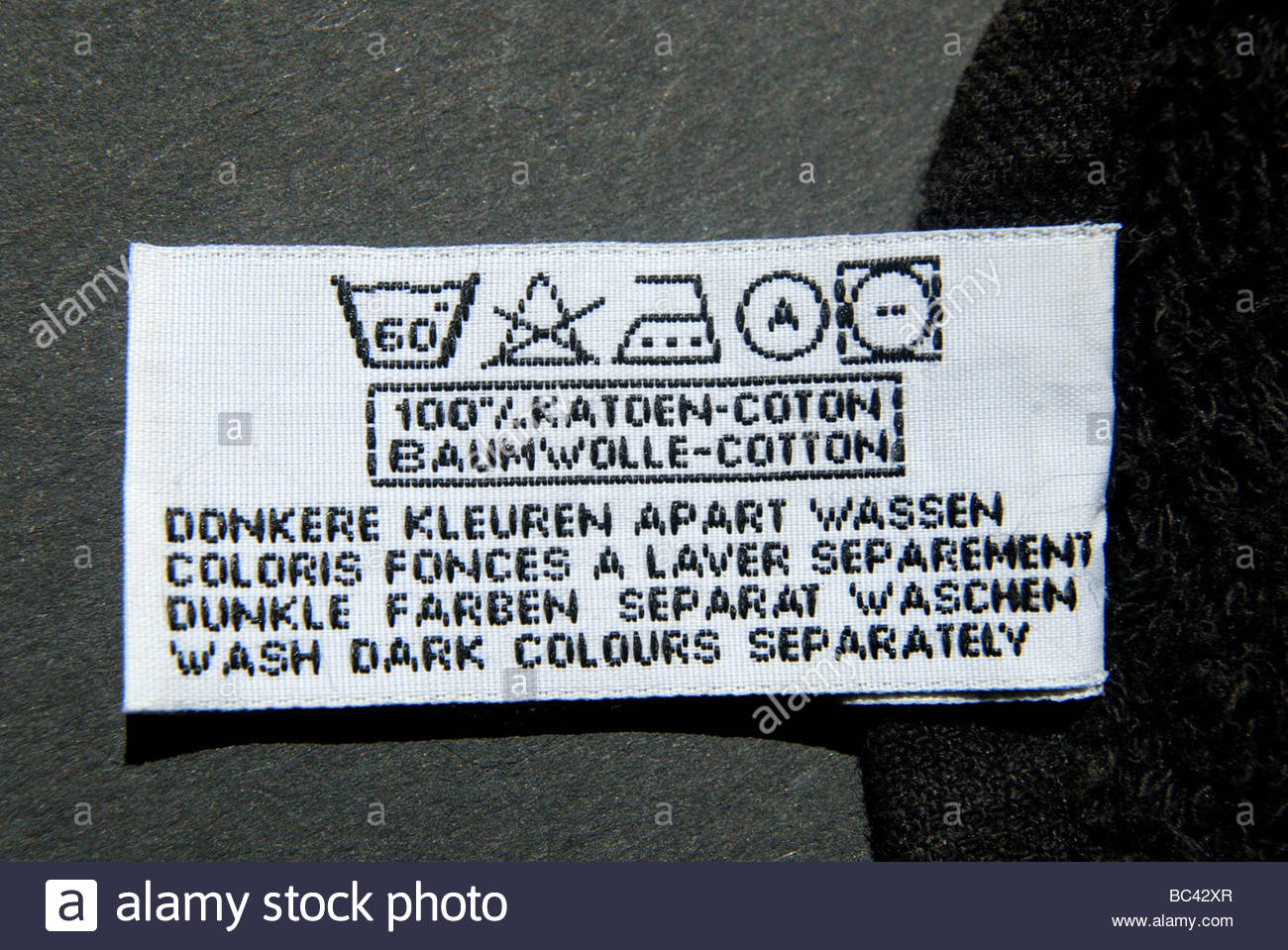 Wash dark colours separately stock photos wash dark colours washing instructions on a black towel in symbols dutch french german and english biocorpaavc