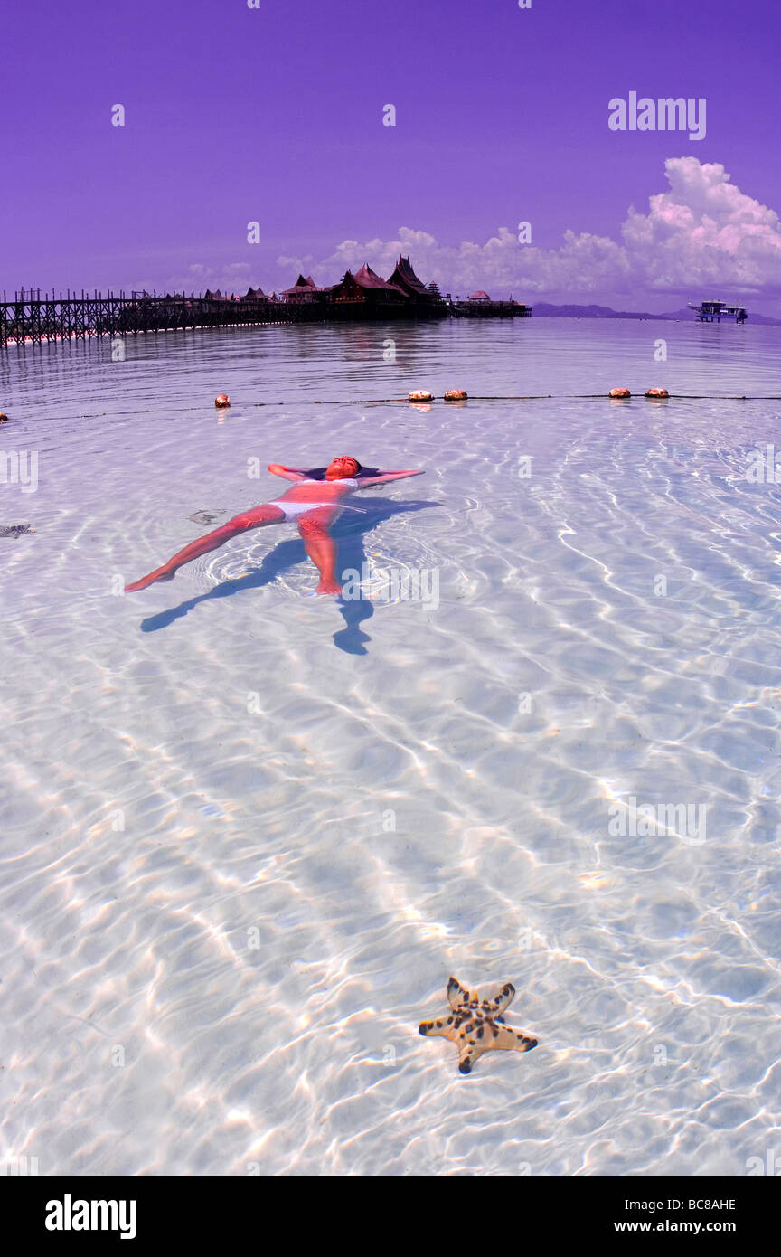 Girl in white bikini floating in shallow water over sand. Holiday ...