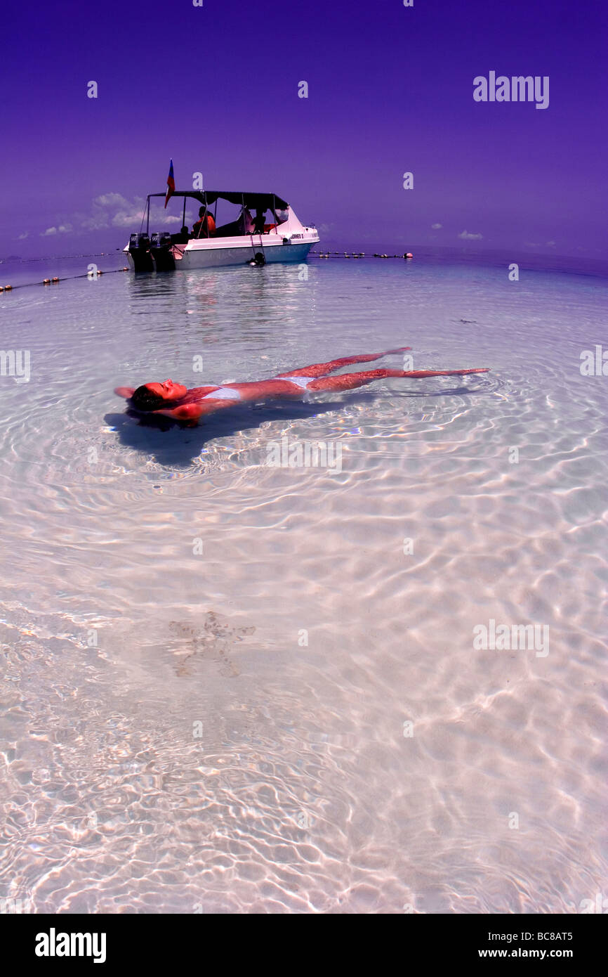 Girl in white bikini floating in shallow water over sand. Dive ...
