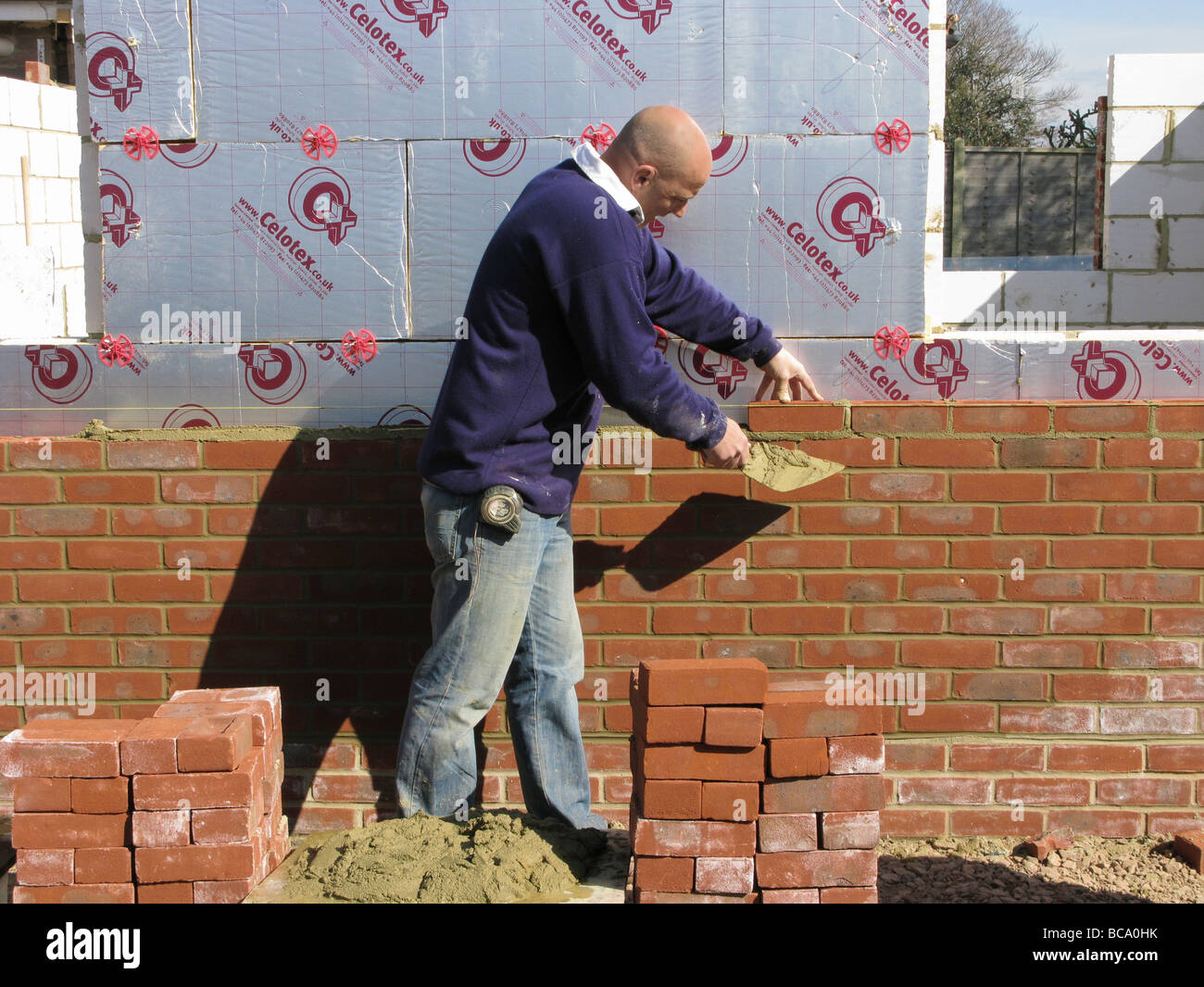 Builder Construction Worker Working On A Brick Wall Cementing Bricks In Showing Celotex Thermal Insulation Board Cavity