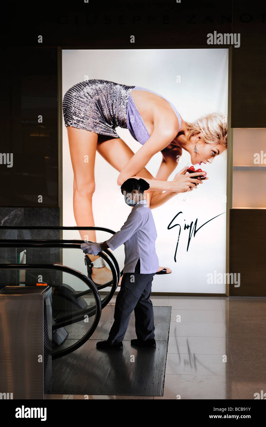 hong kong cleaning lady in front of fashion beauty advertisement hong kong cleaning lady in front of fashion beauty advertisement in the mall of the international