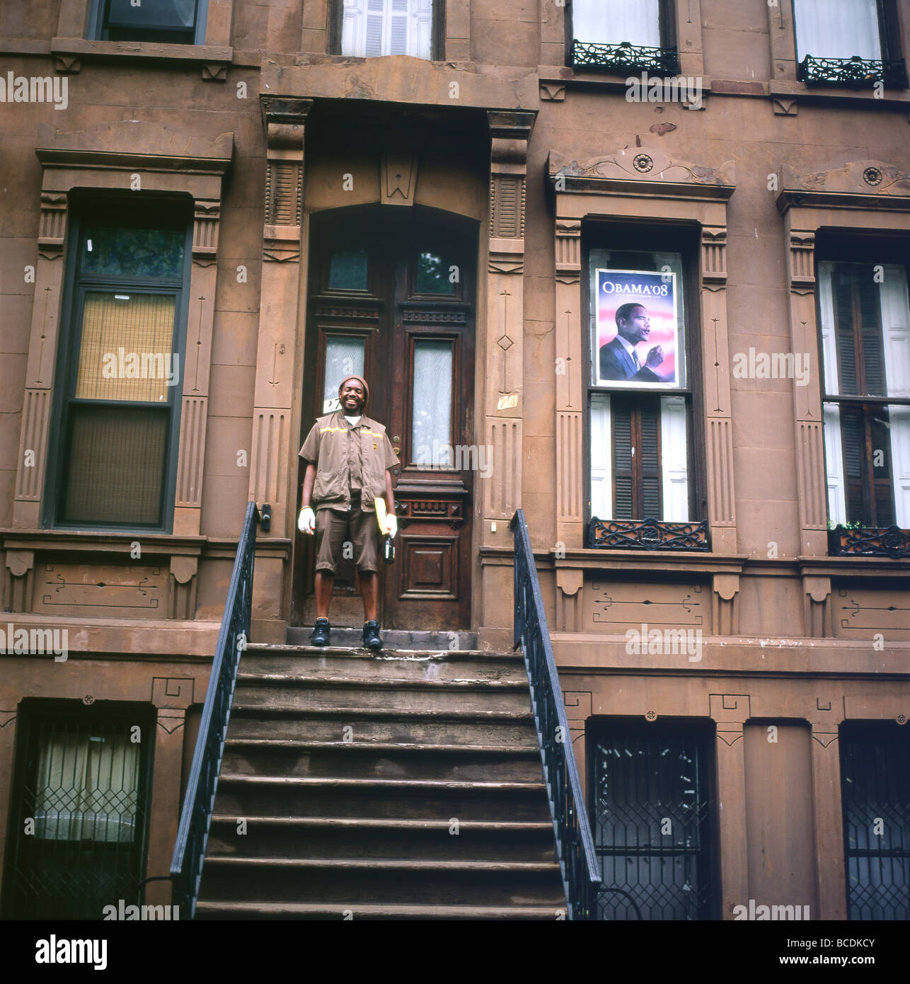 Harlem New York Apartments: A Delivery Man Standing On The Steps Of A Brownstone