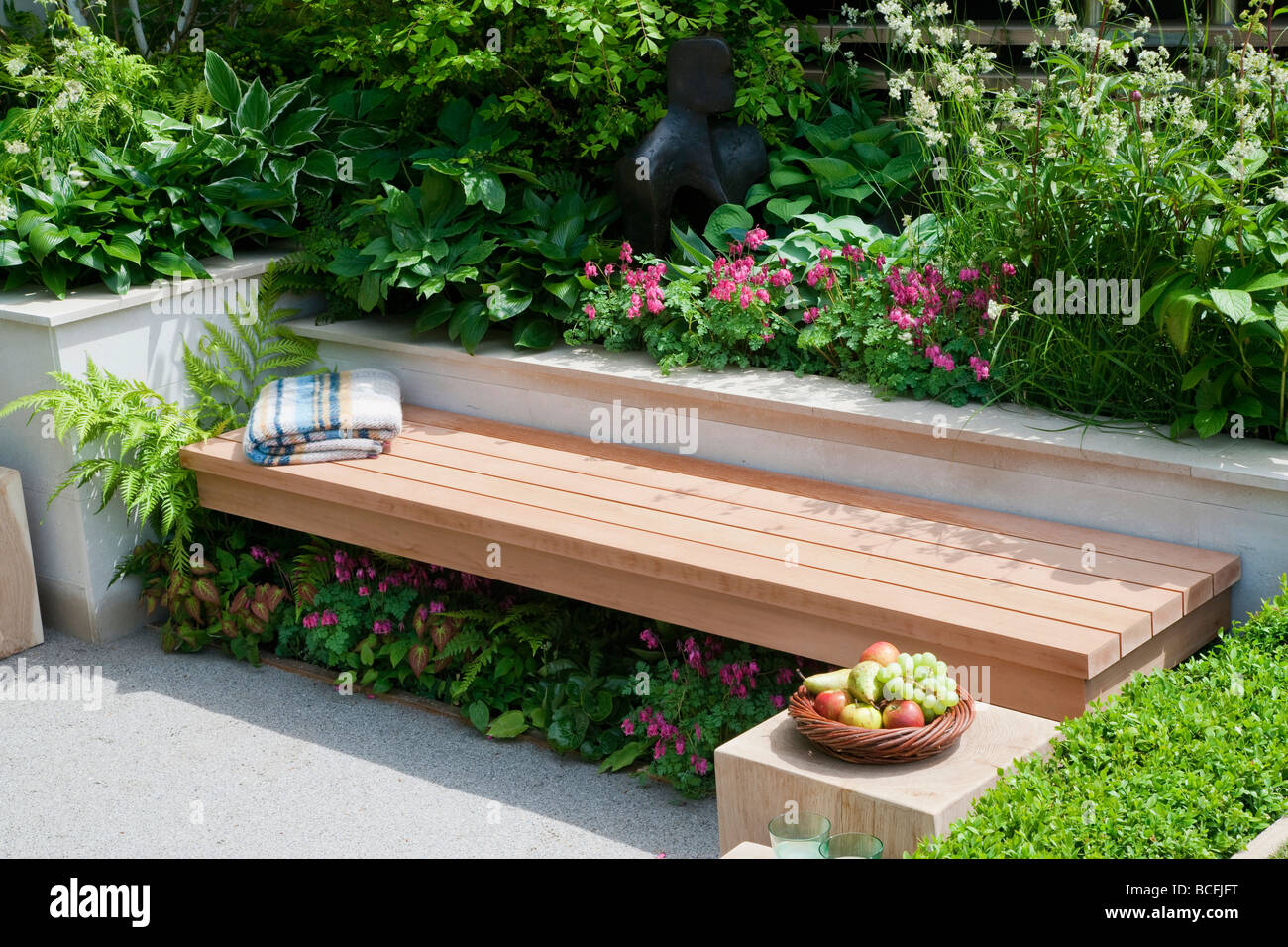 Wooden Bench Surrounded By Geometric Raised Beds. Plants Include Hostas,  Ferns, Dicentra Formosa Cultivar And Peonies
