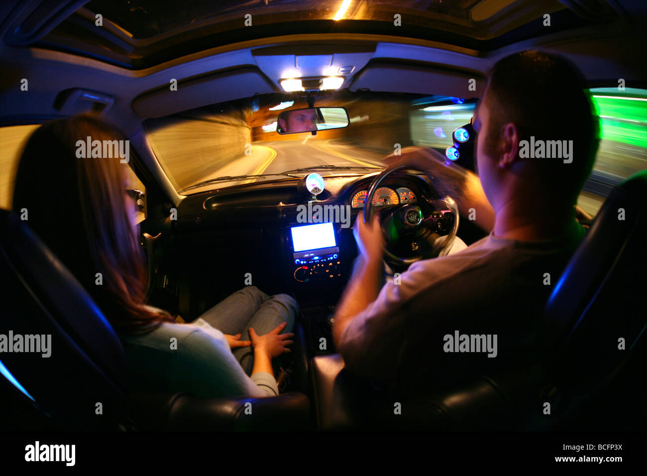 young man and girl driving through town at night in a