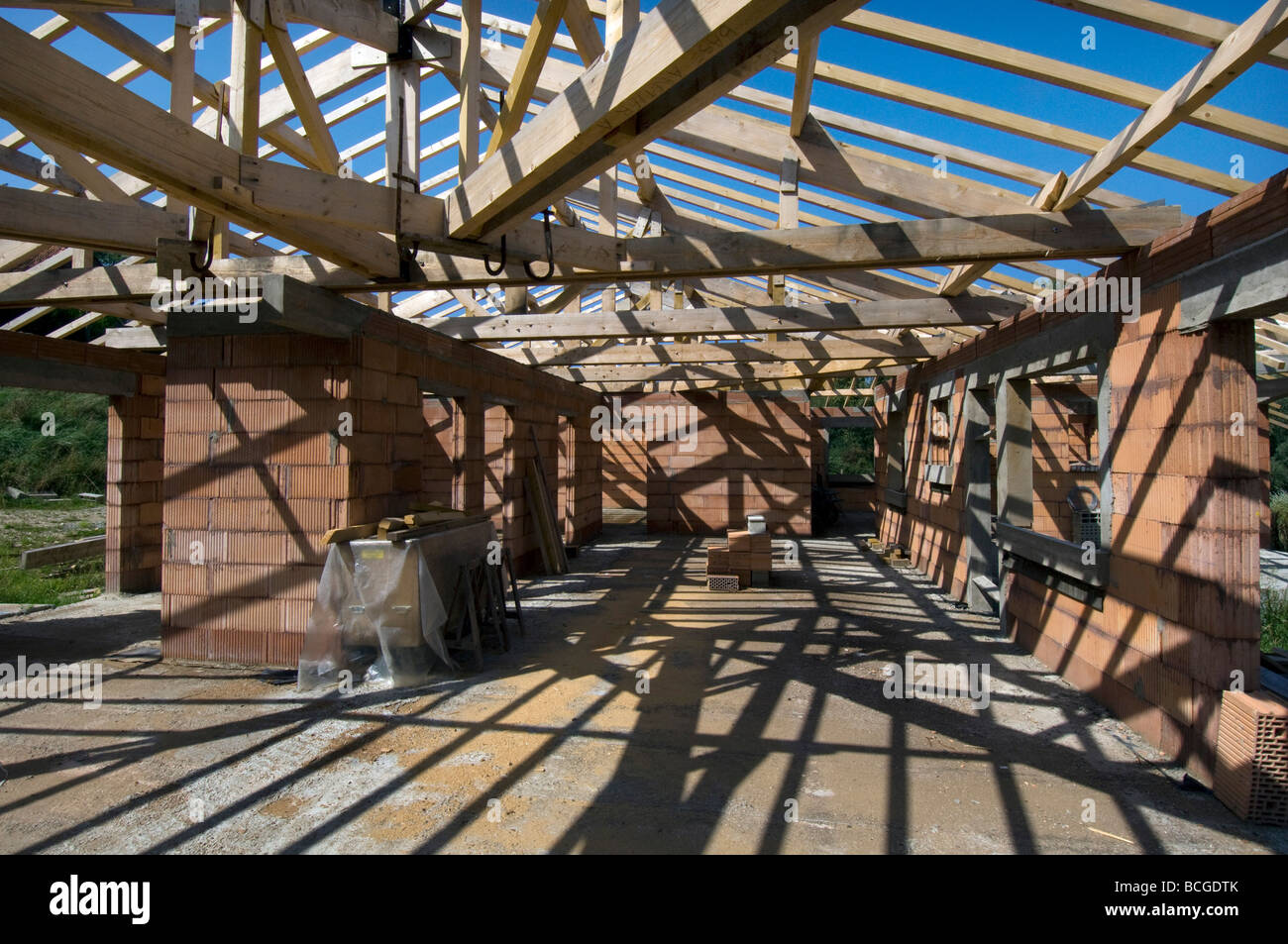 Shadows of roof trusses and wooden beams criss cross the for Roof and floor