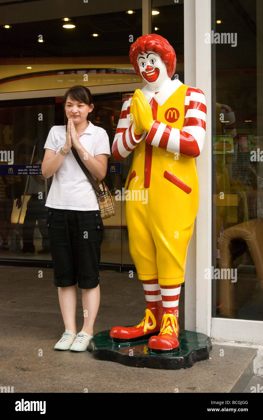 Ronald mcdonald greeting customers with the traditional thai ronald mcdonald greeting customers with the traditional thai greeting called a wai at the entrance to a mcdonalds restaurant kristyandbryce Images